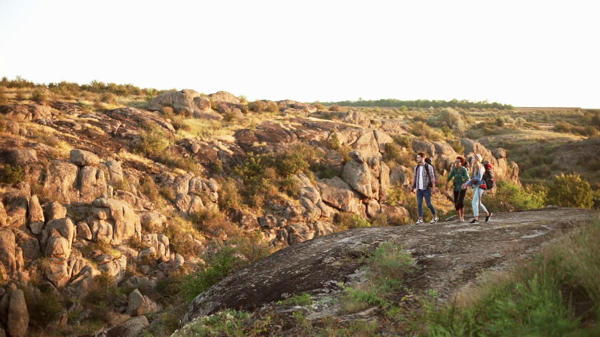 Three friends walking in rocky landscape with camping backpacks ...
