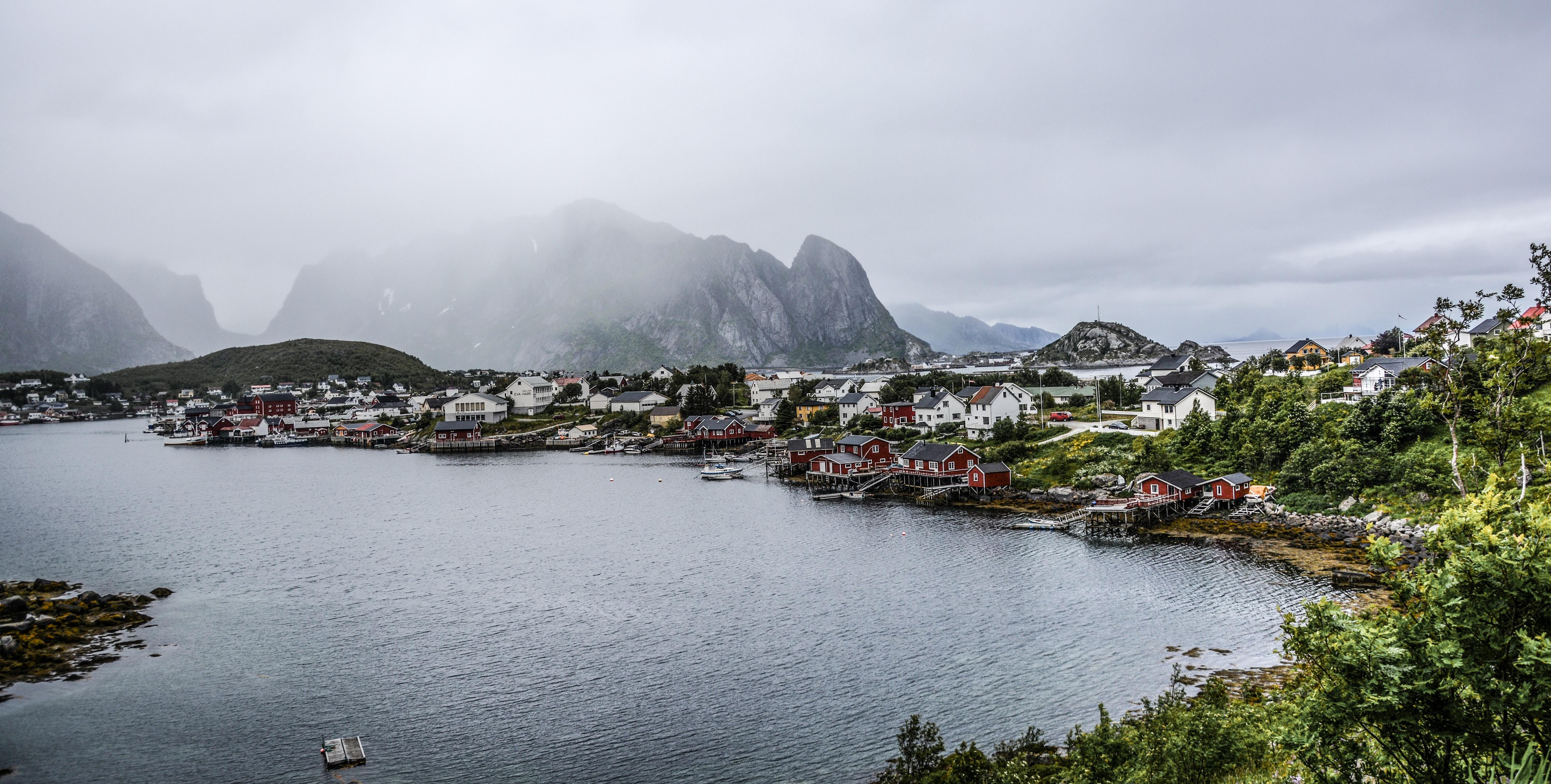 Rocky mountain near citizen houses near body of water photo
