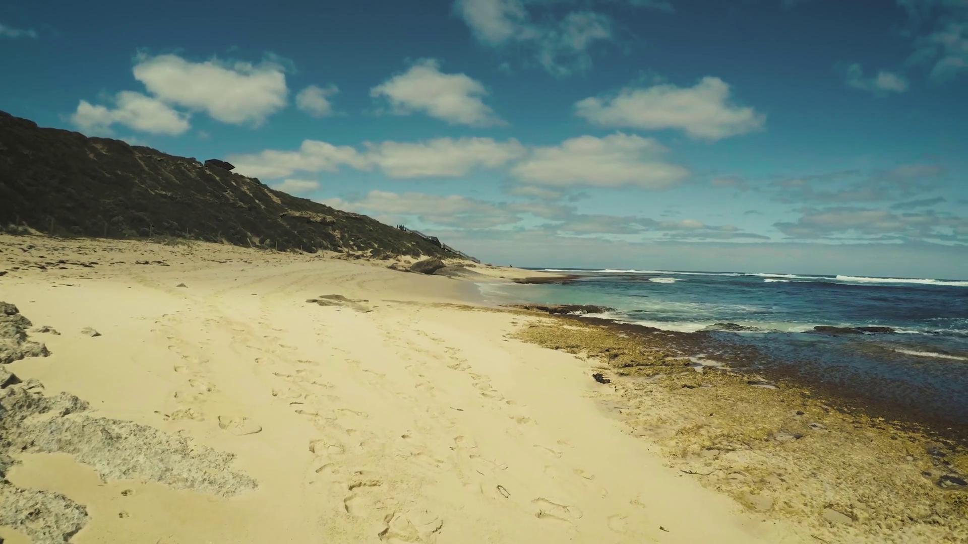 Walking on an ocean rocky sand beach, shot in 4k first person ...