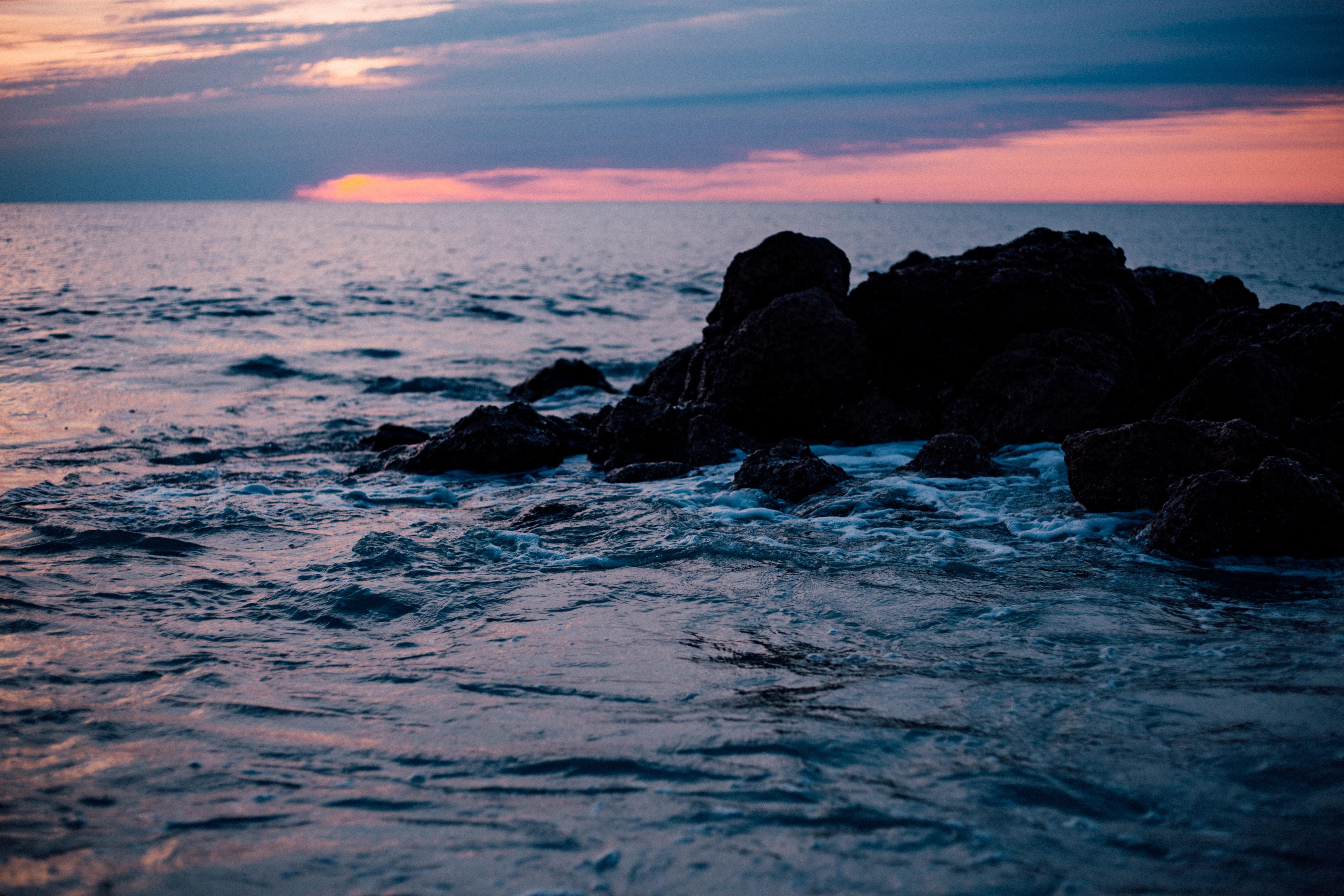 Rocky sea shore during sun set photo