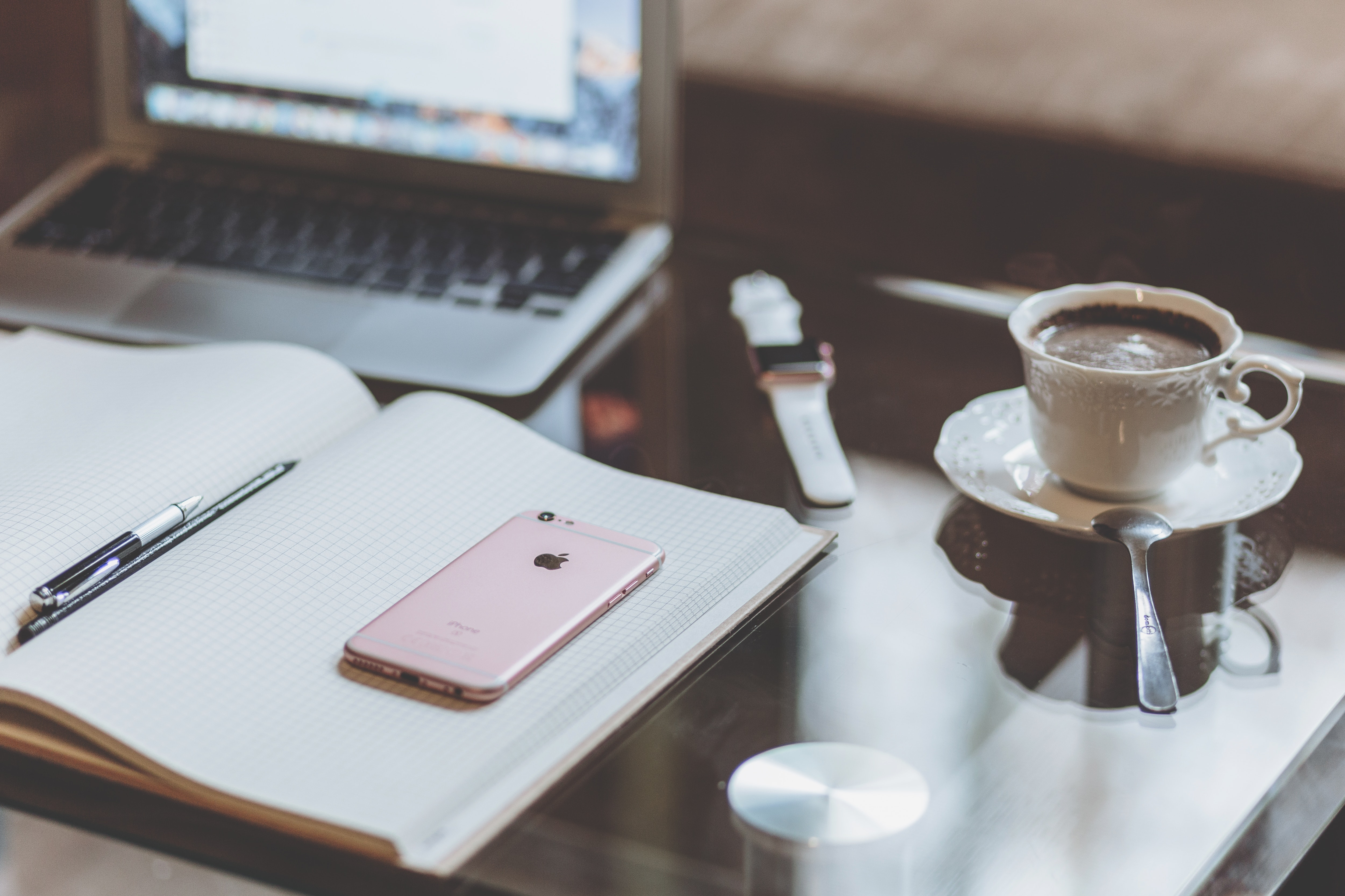 Rose gold iphone 6s on white book near coffee photo
