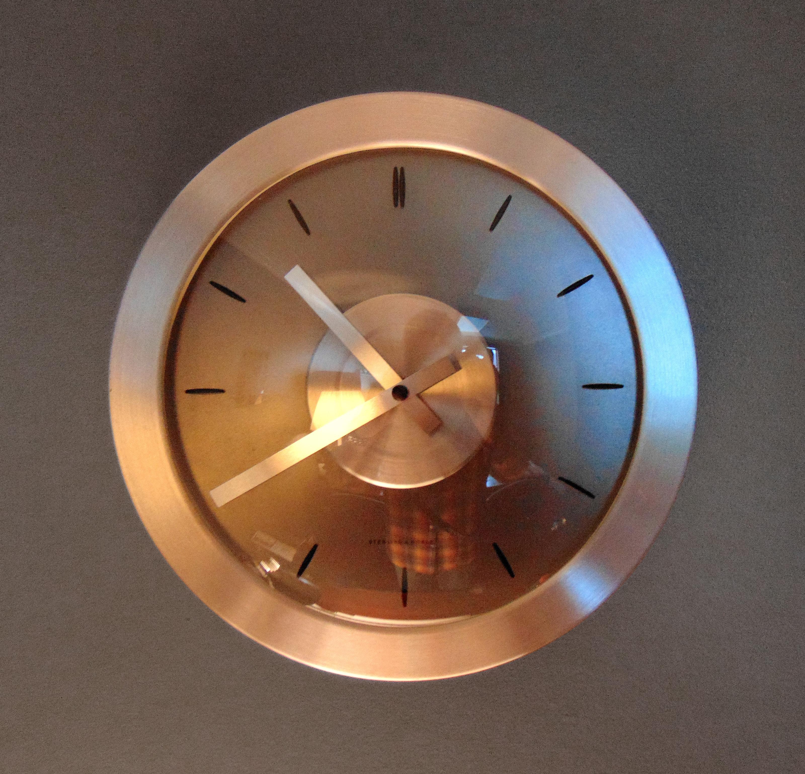 Round bronze analog wall clock photo