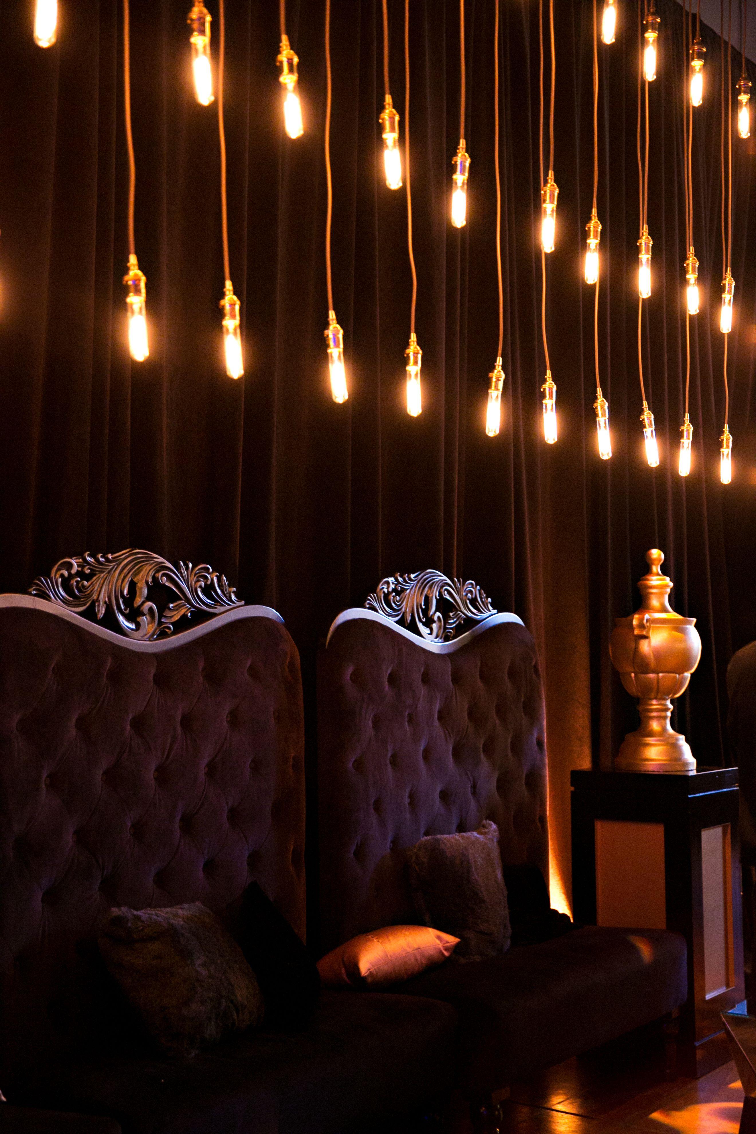 Rows of vintage bulbs create a dynamic backdrop against black drape ...