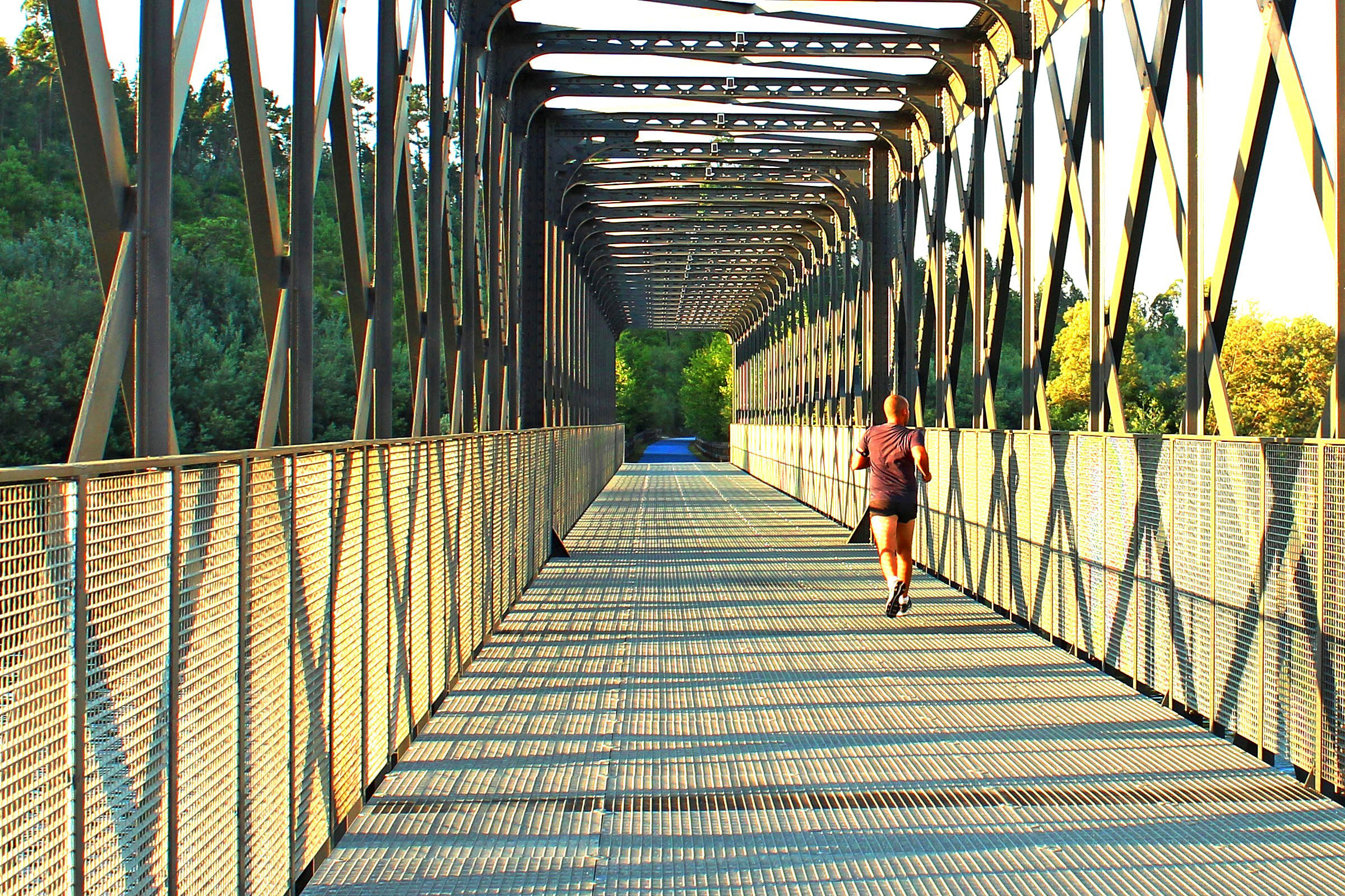 Runner crossing a metal bridge photo