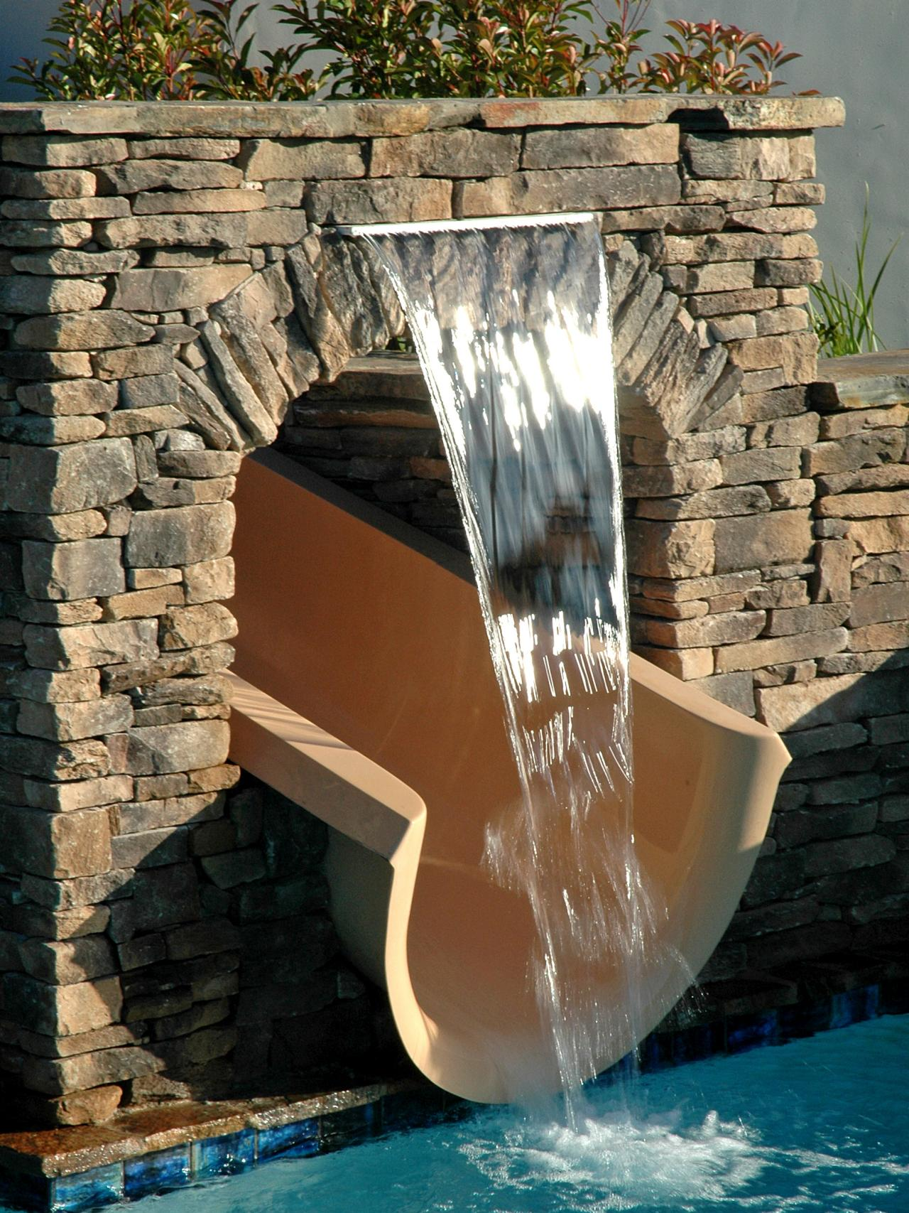 Modern Pool Slide With Playful Stone Tunnel Featuring Cream Slide ...