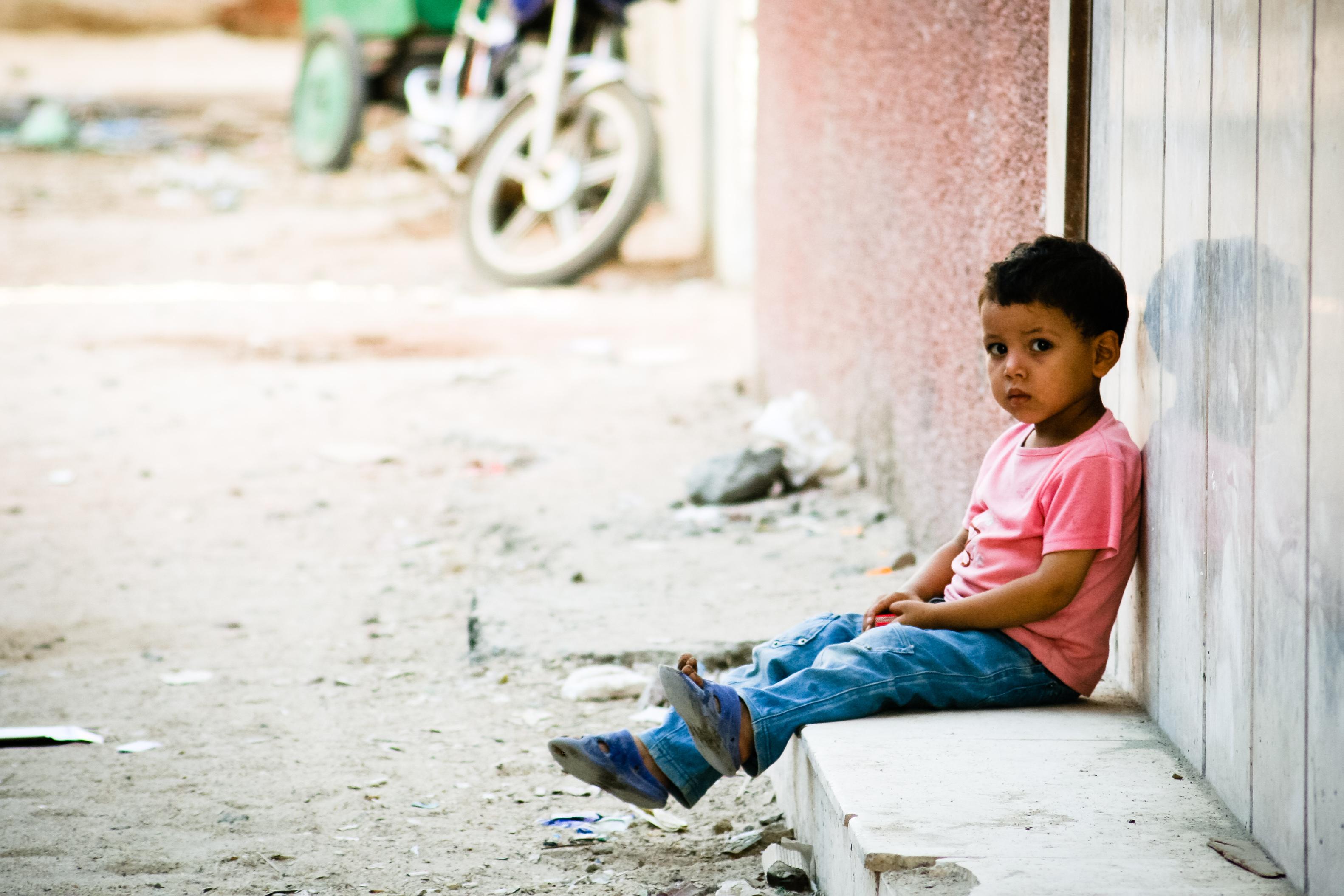 Sad little boy waiting outside photo