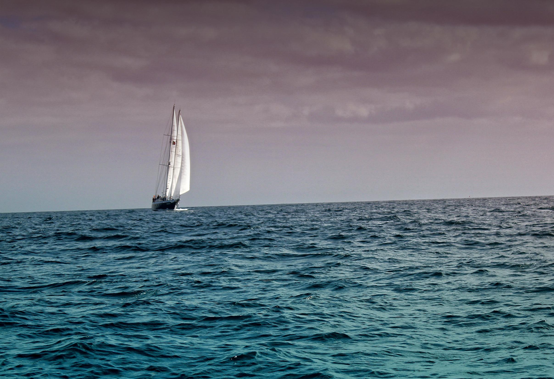 Sail boat under dark skies photo