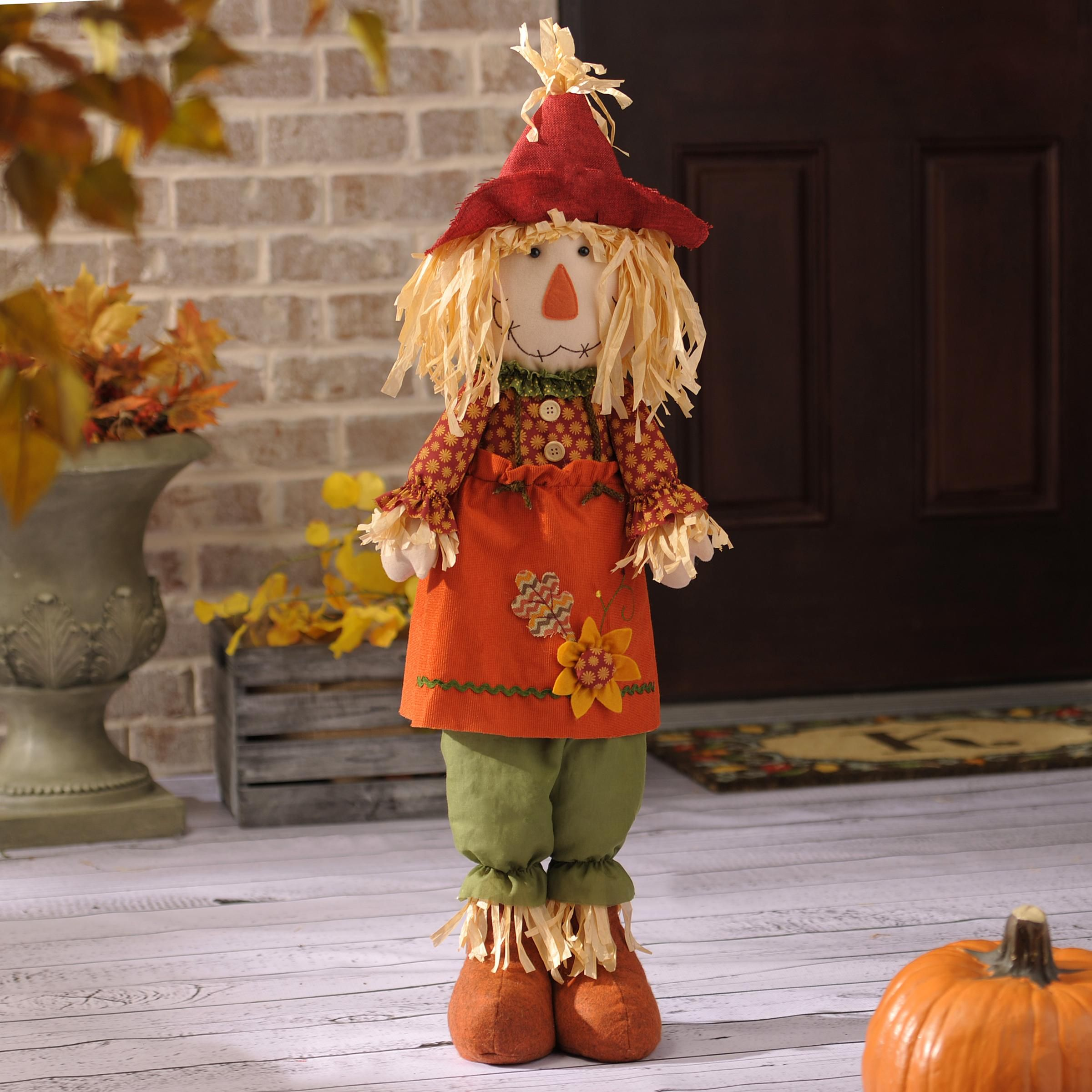 Scarecrow standing with pumpkins photo