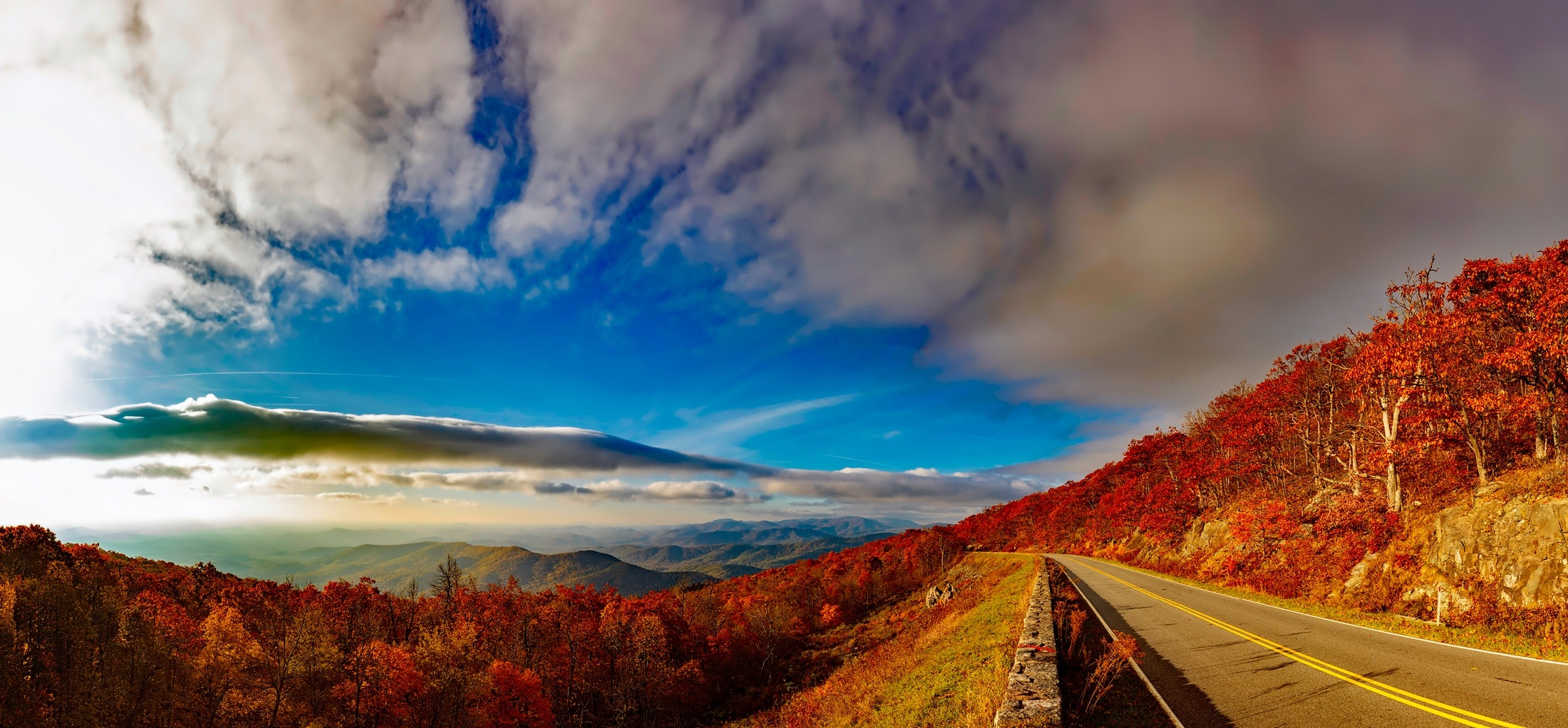Scenic view of mountain road against cloudy sky photo