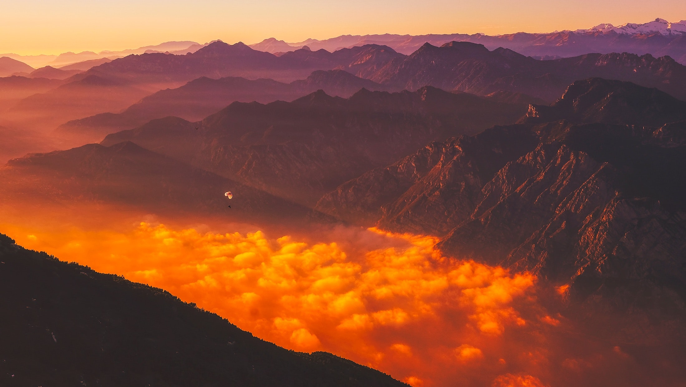 Scenic view of mountains against dramatic sky at sunset photo