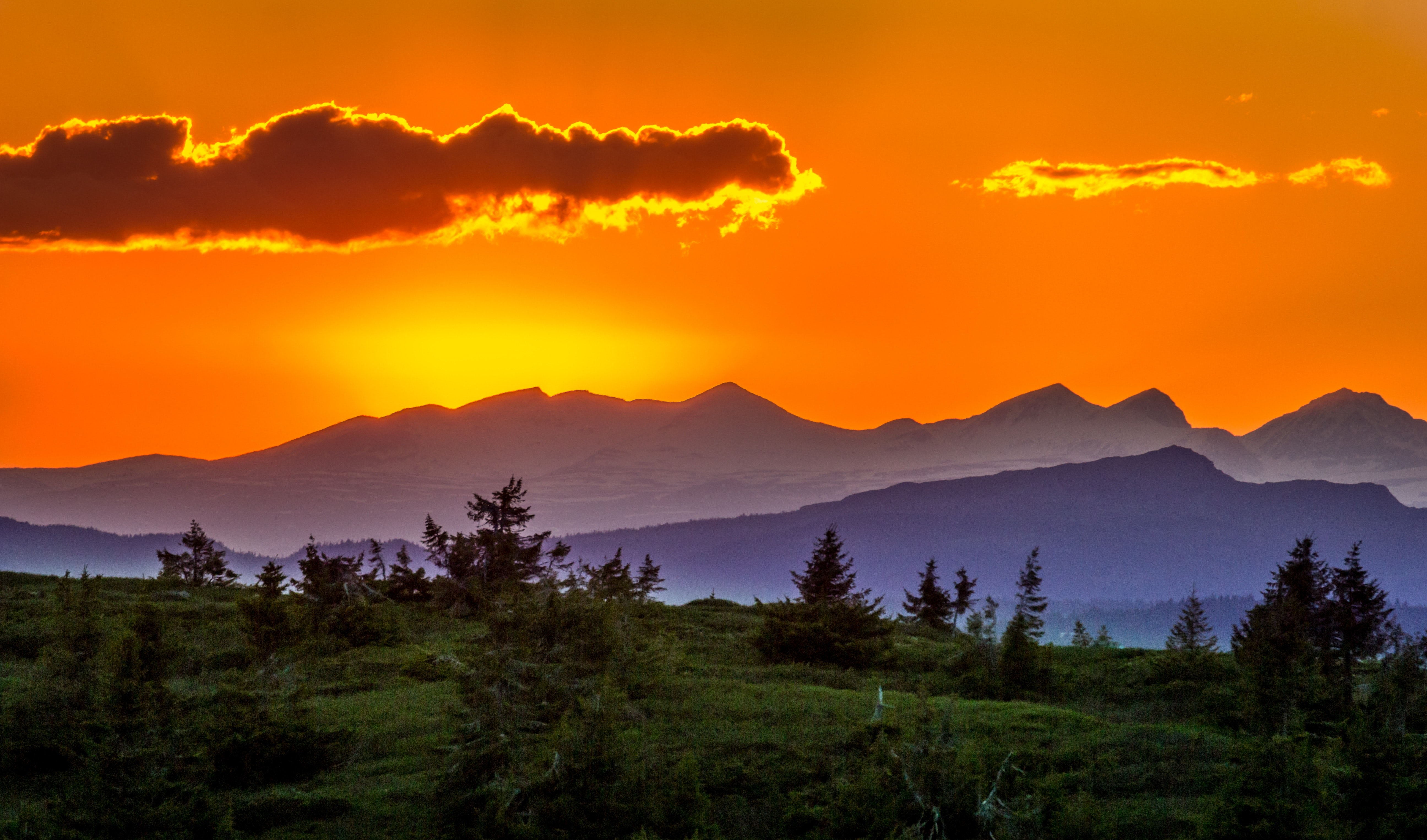 Scenic view of mountains against sky at sunset photo