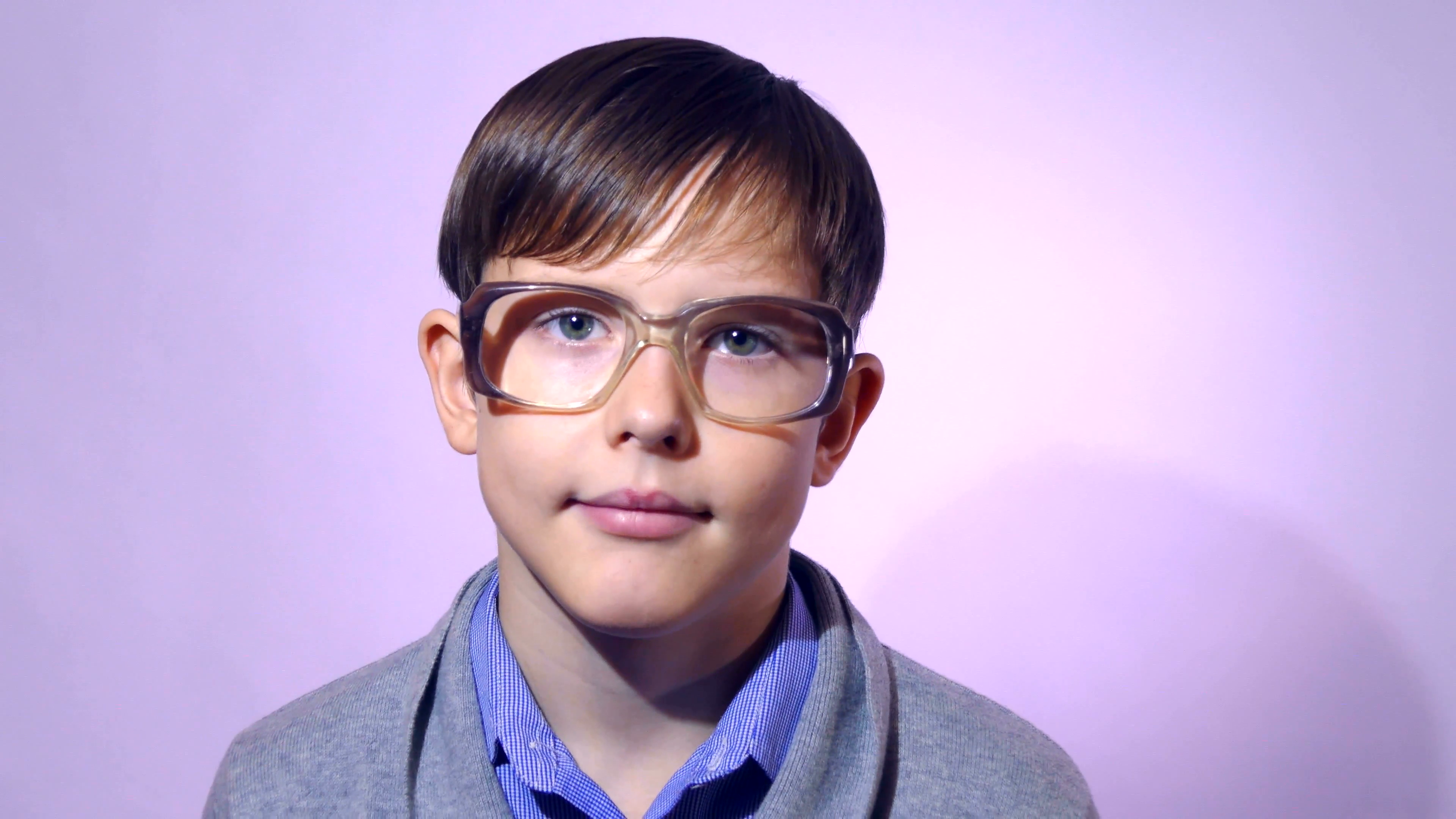 Portrait of boy teenager schoolboy nerd glasses on purple background ...