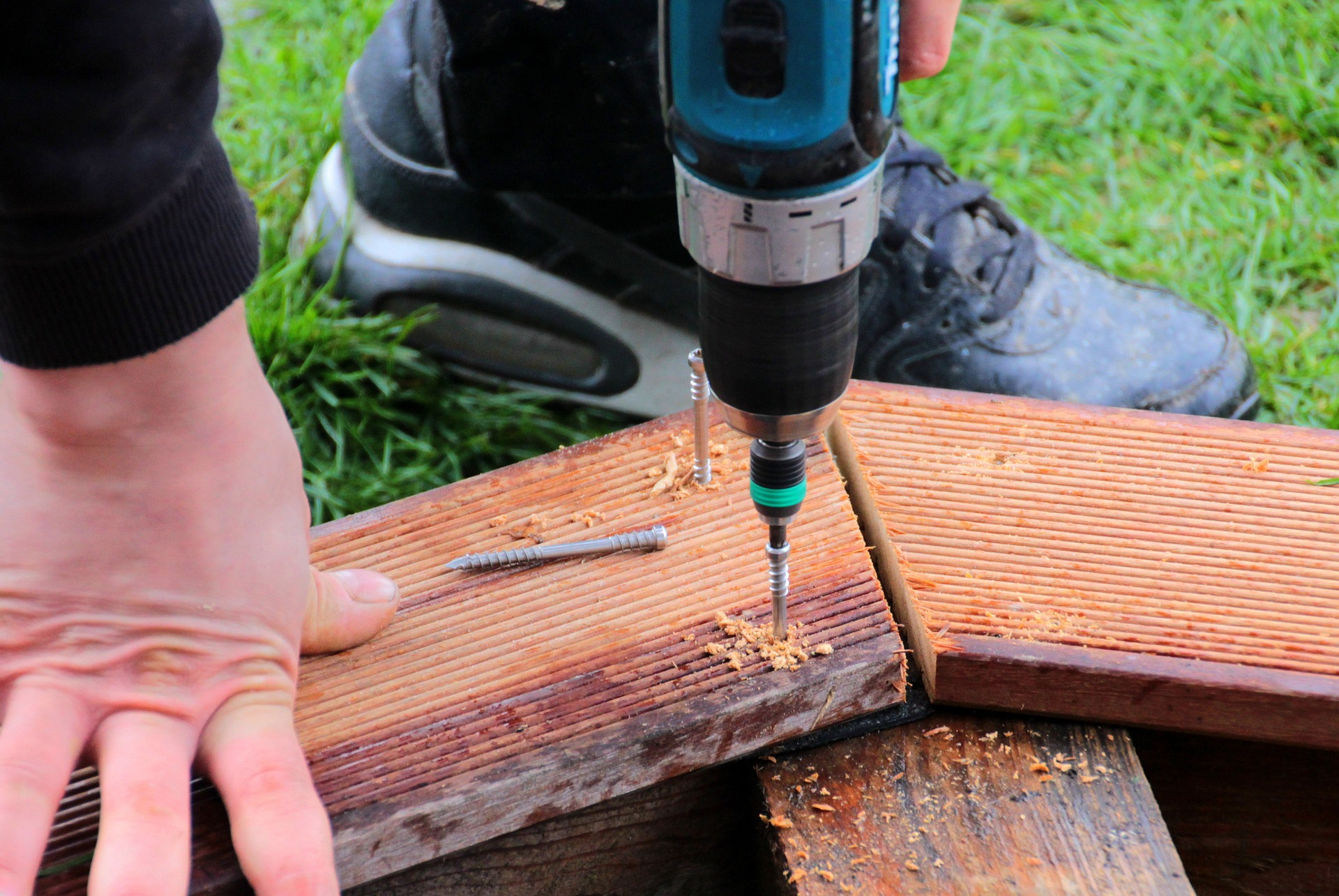 Screwing wooden board with a drill photo