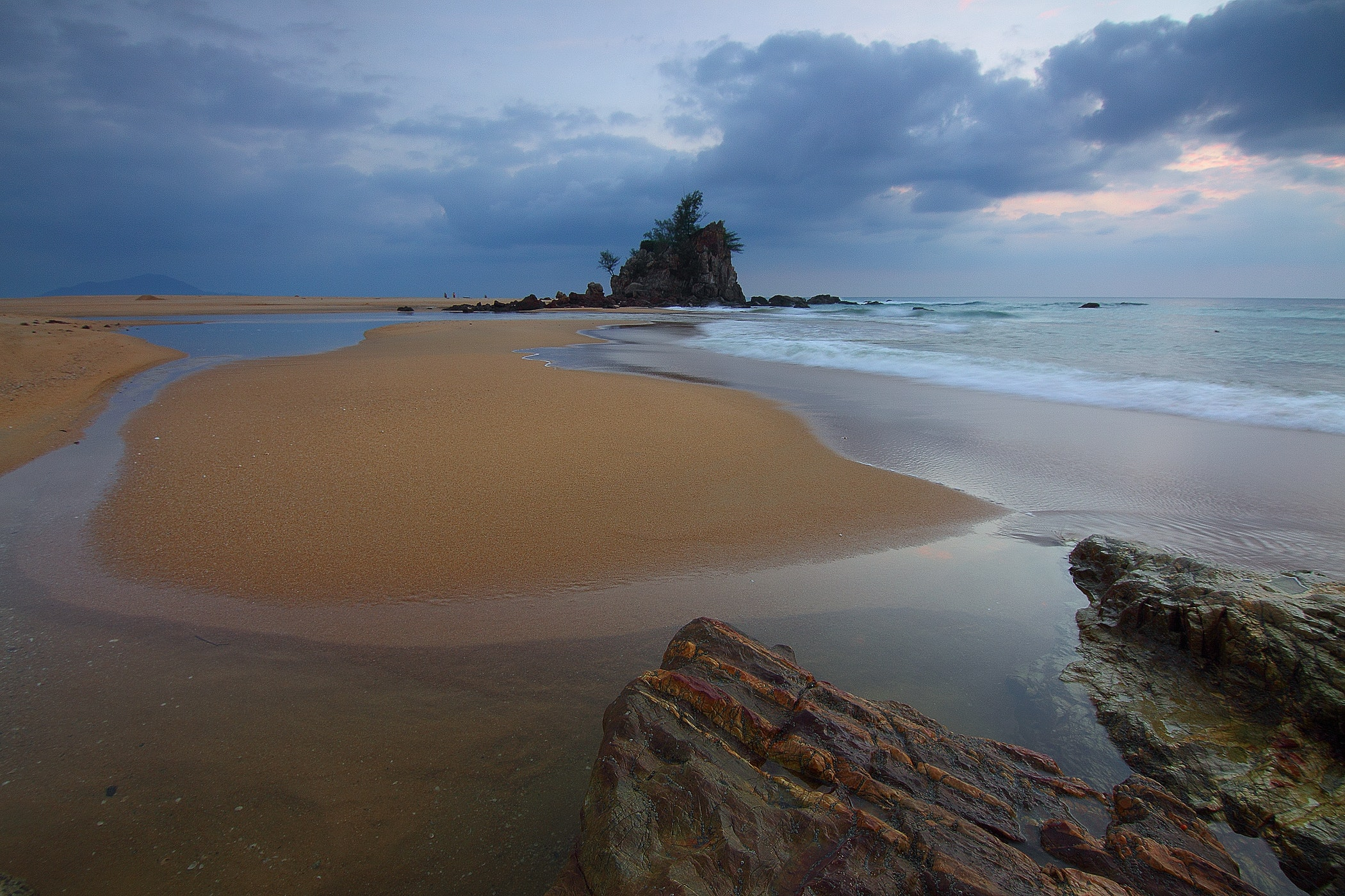 Sea wave crashing on seashore with view of rock formation with trees on top of it under grey clouds and white sky photo