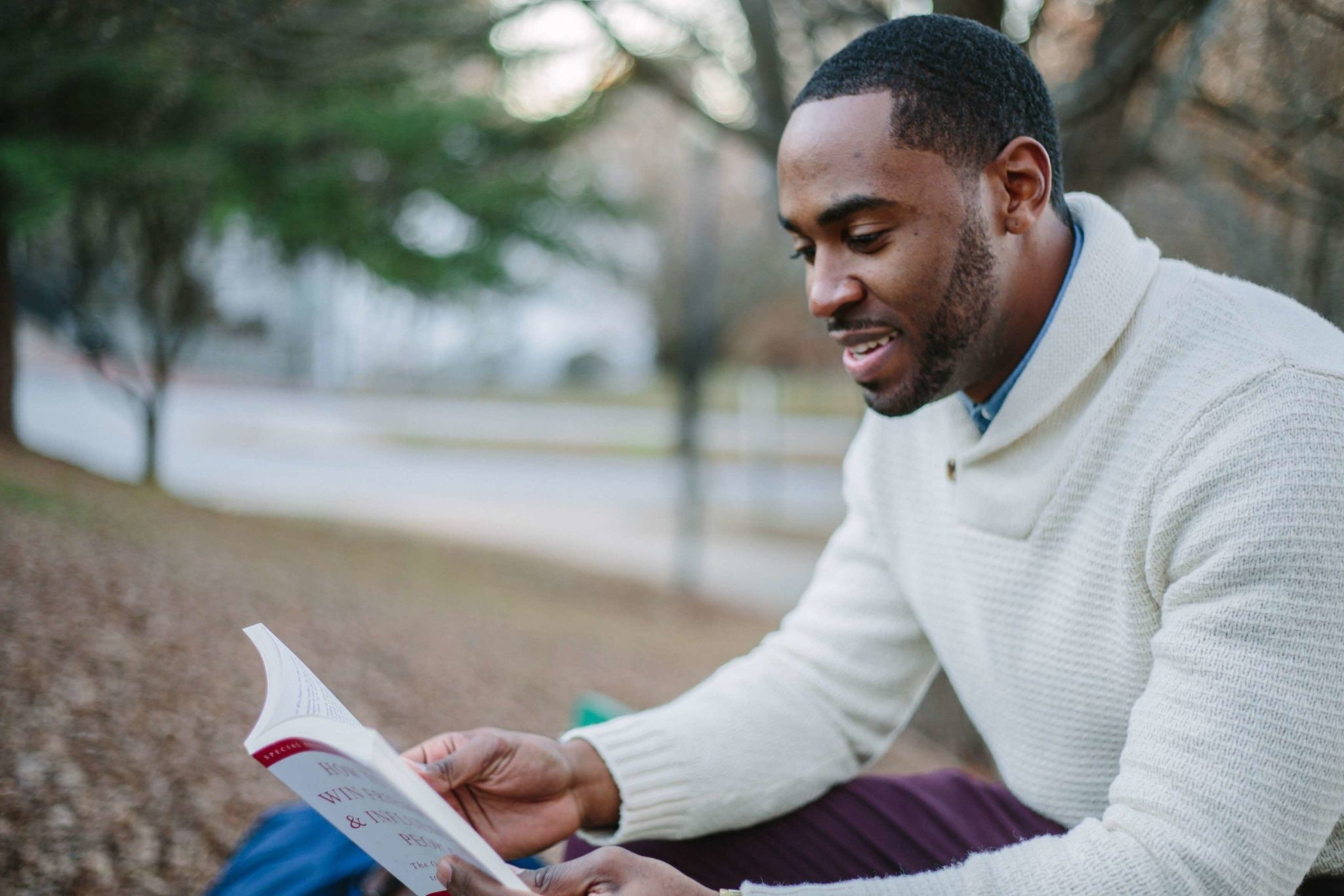 Selective focos photography of man in white sweater reading book