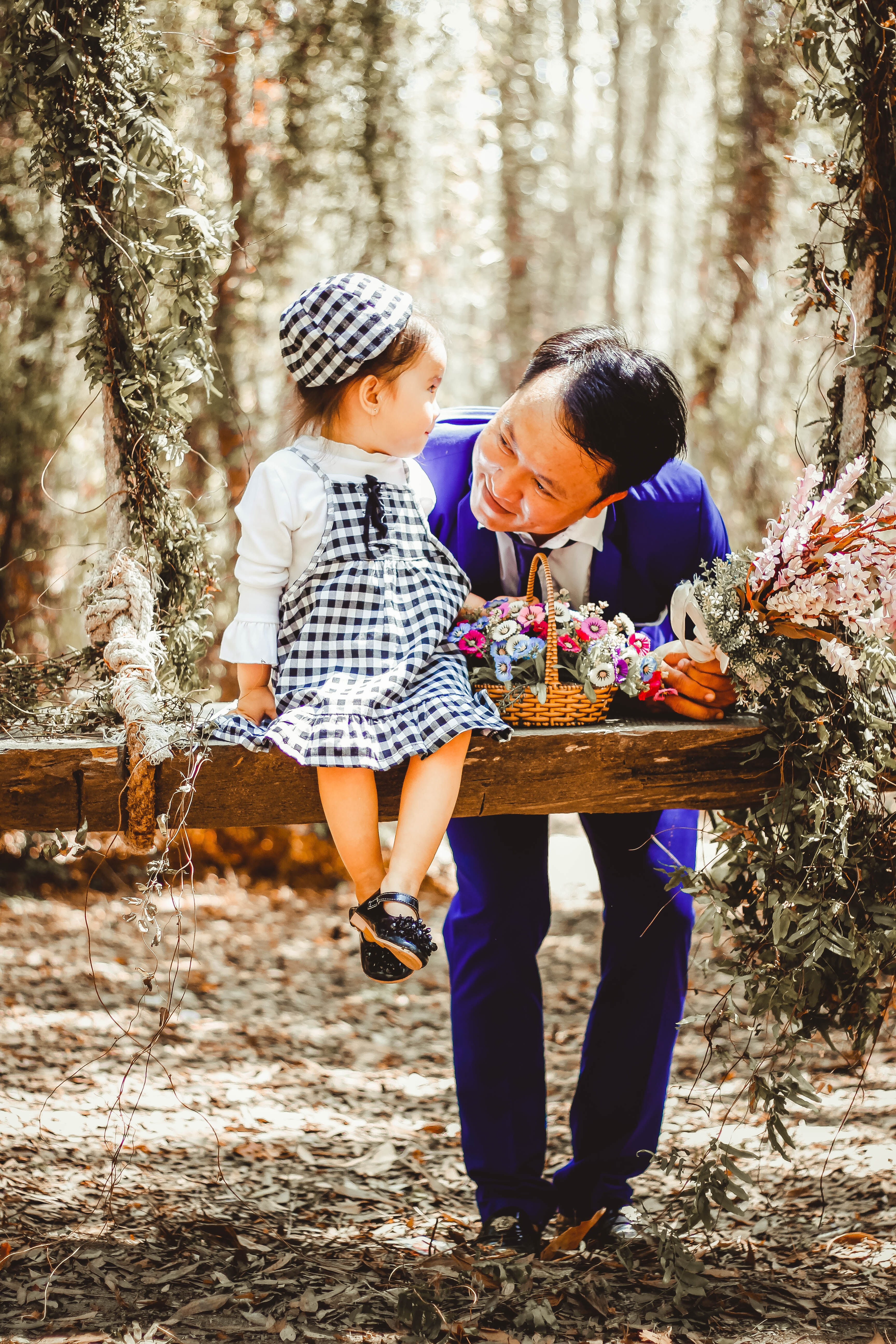 Selective Focus and Color Photography of Man Looking at Her Girl Sitting on Garden Swing White Holding Bouquet of Flower in Brown Wicker Basket, Smiling, People, Park, Together, HQ Photo