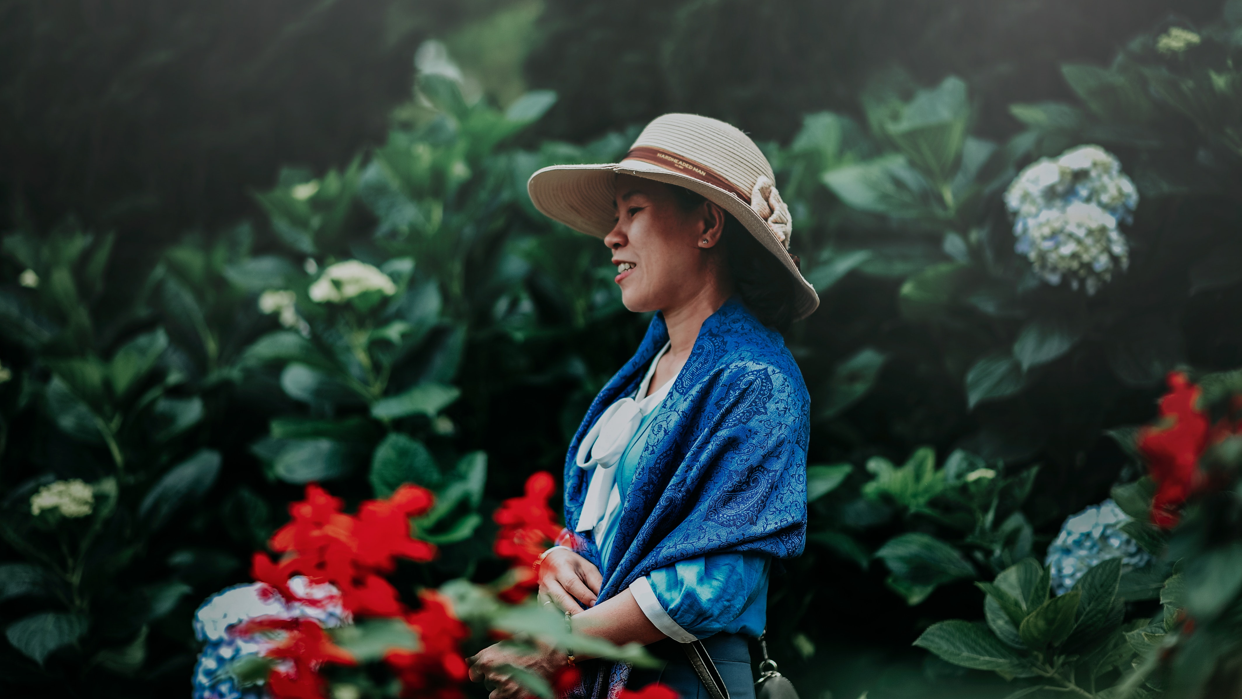 Selective Focus Photo of Woman in Blue Shawl and Brown Sun Hat in the Middle of Garden, Colors, Face, Flowers, Garden, HQ Photo