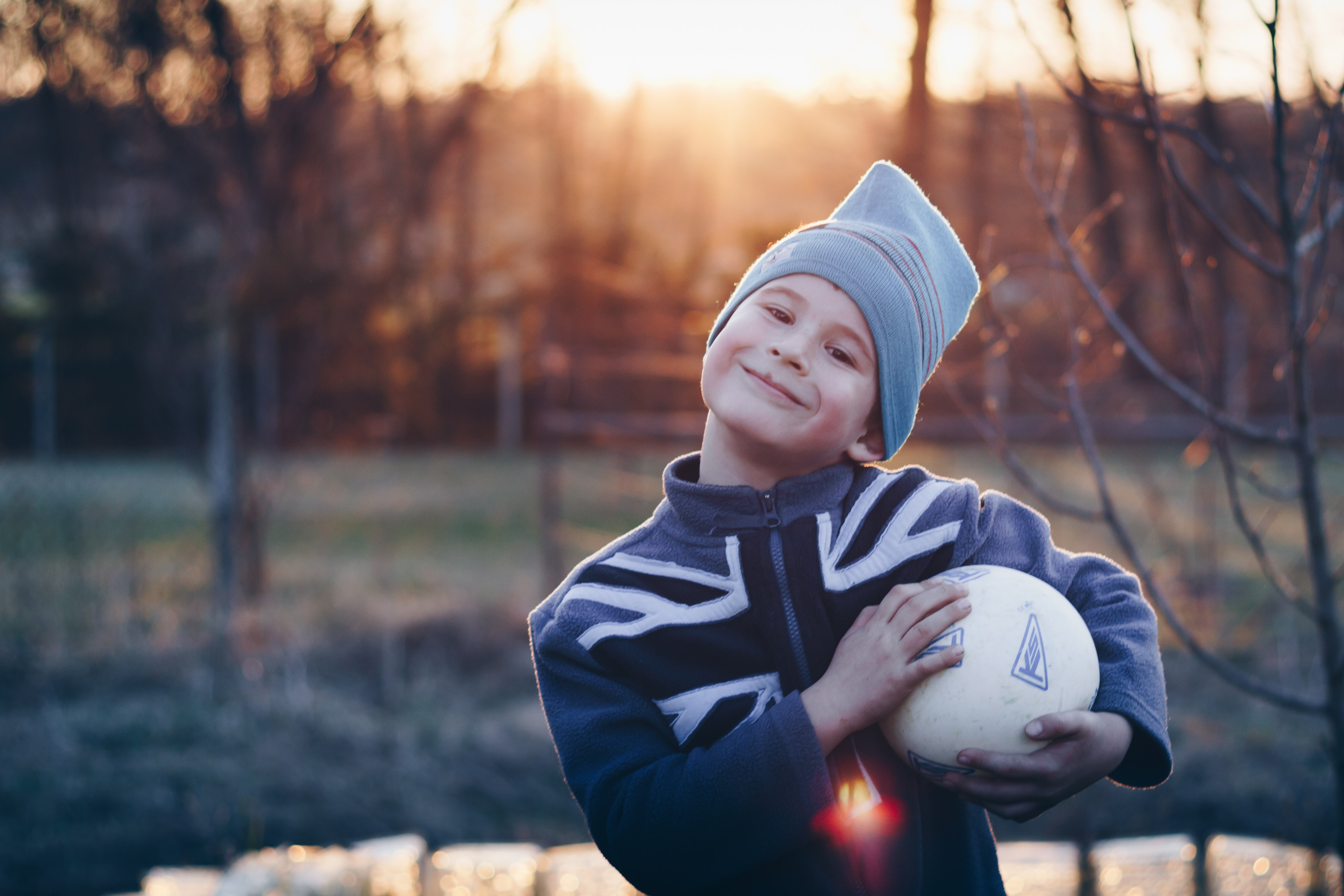 Selective Focus Photography of Boy Wearing Blue United Kingdom Print Zip-up Jacket Carrying White Ball, Person, Young, Wear, Trees, HQ Photo