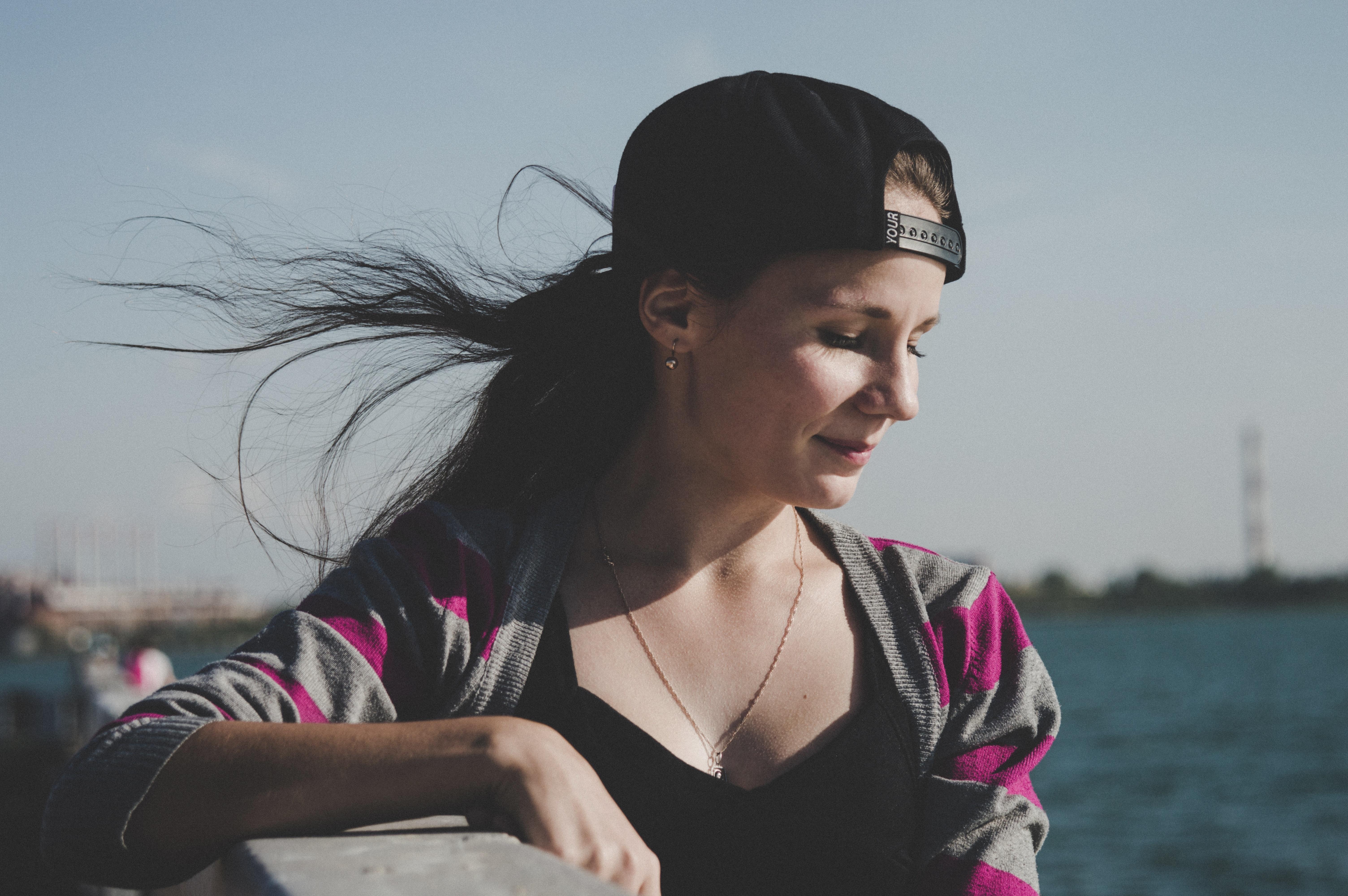 Selective focus photography of female wearing black snapback near ocean
