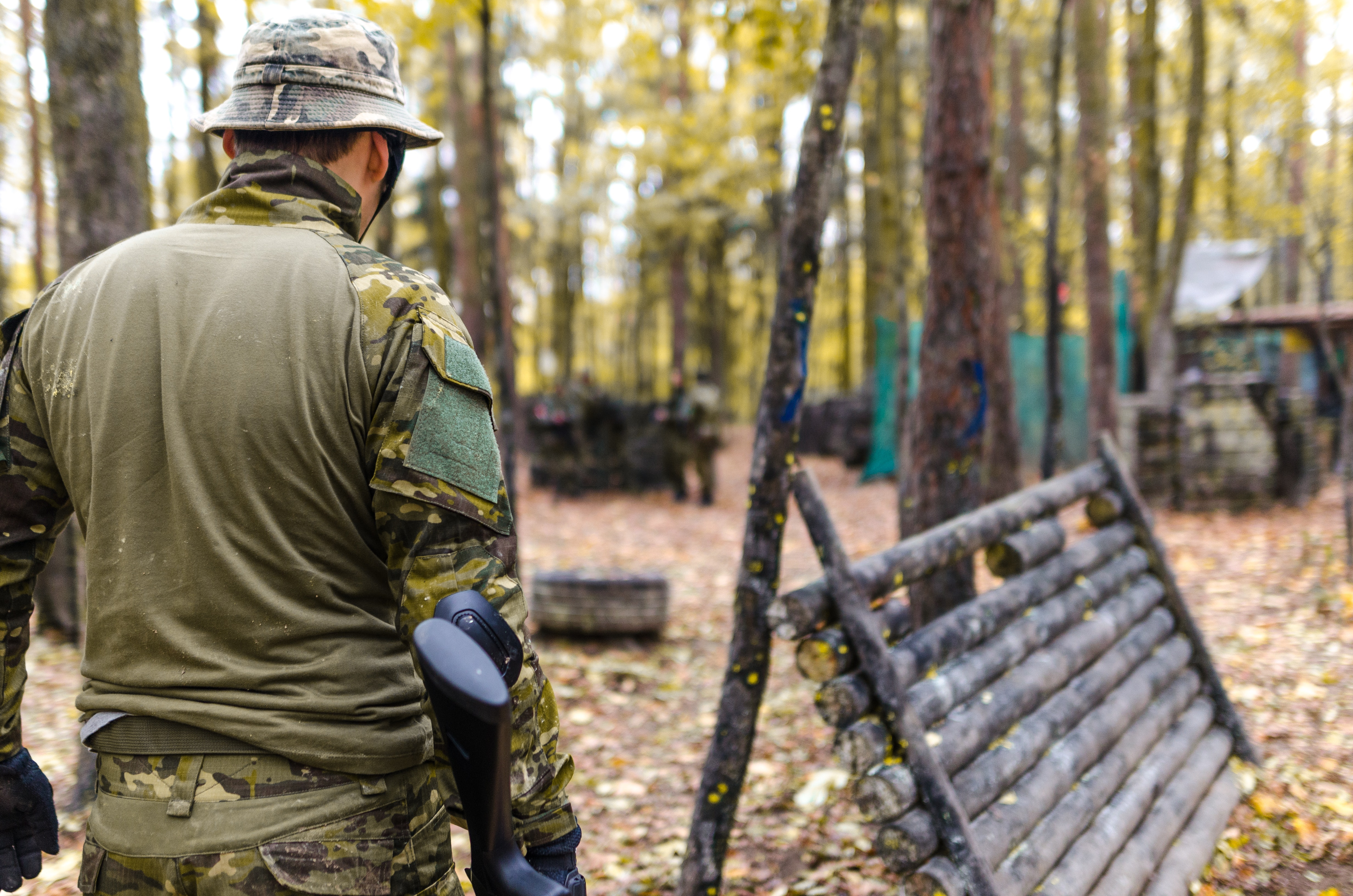 Selective focus photography of man wearing camoflouge suit while holding a gun
