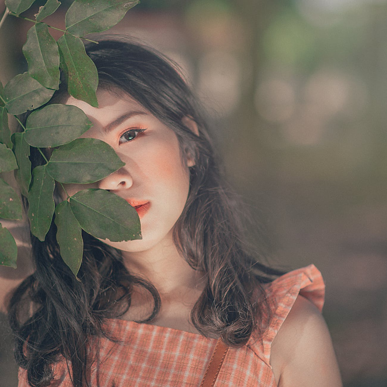 Selective focus photography of woman in orange sleeveless top hiding face behind tree's leaf