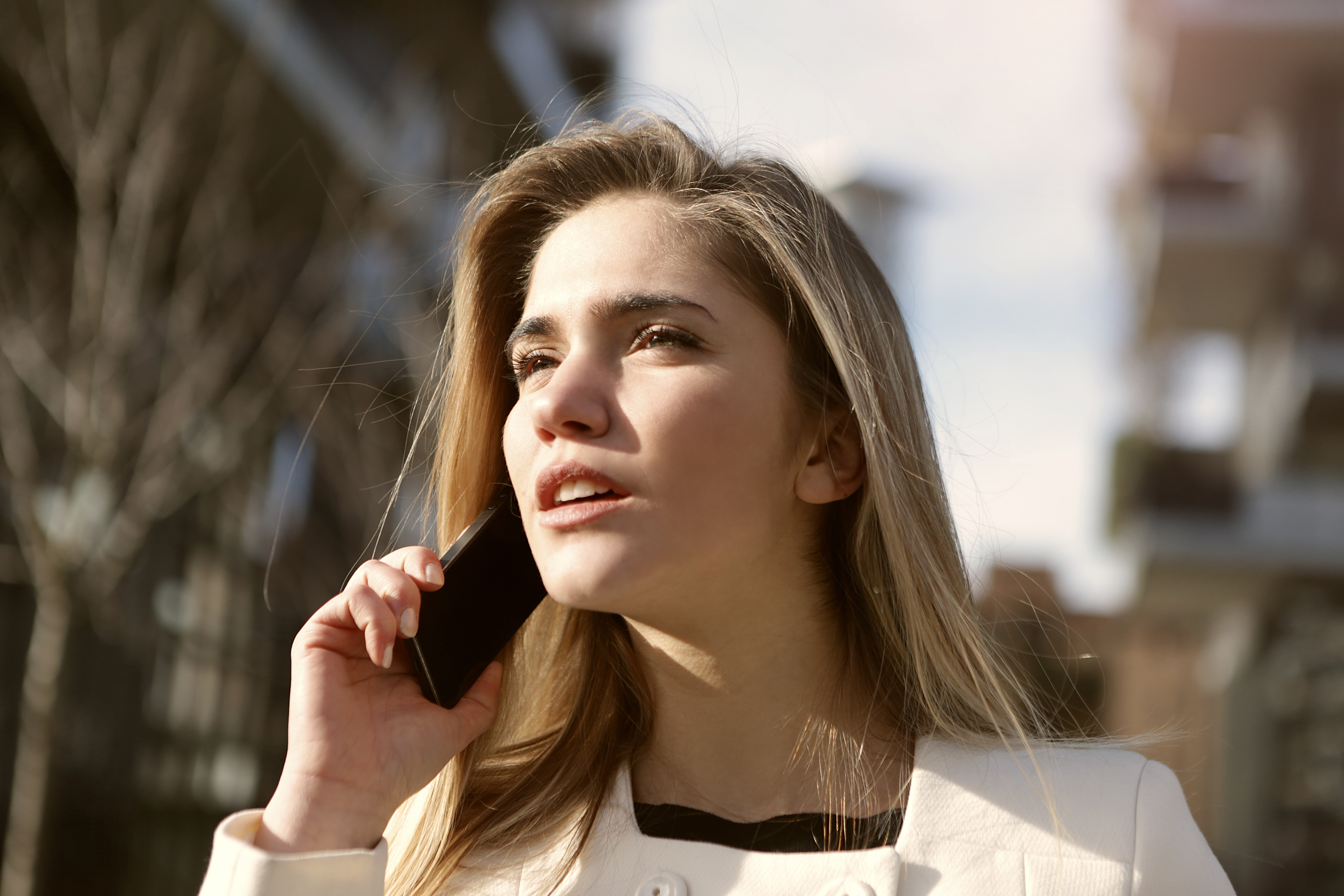 Selective focus photography of woman standing wearing white coat holding smartphone