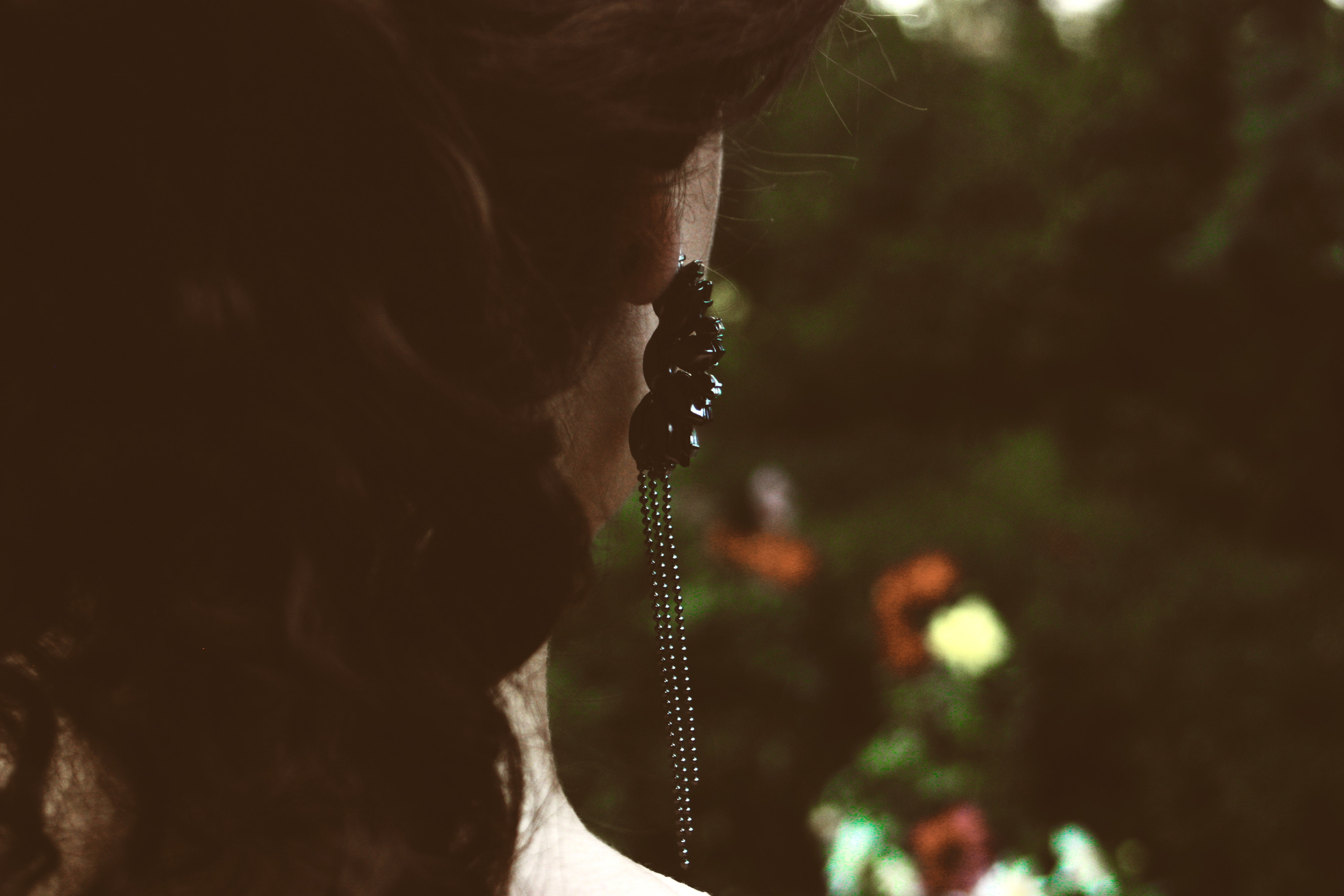 Selective focus photography of woman's back with black pendant earrings