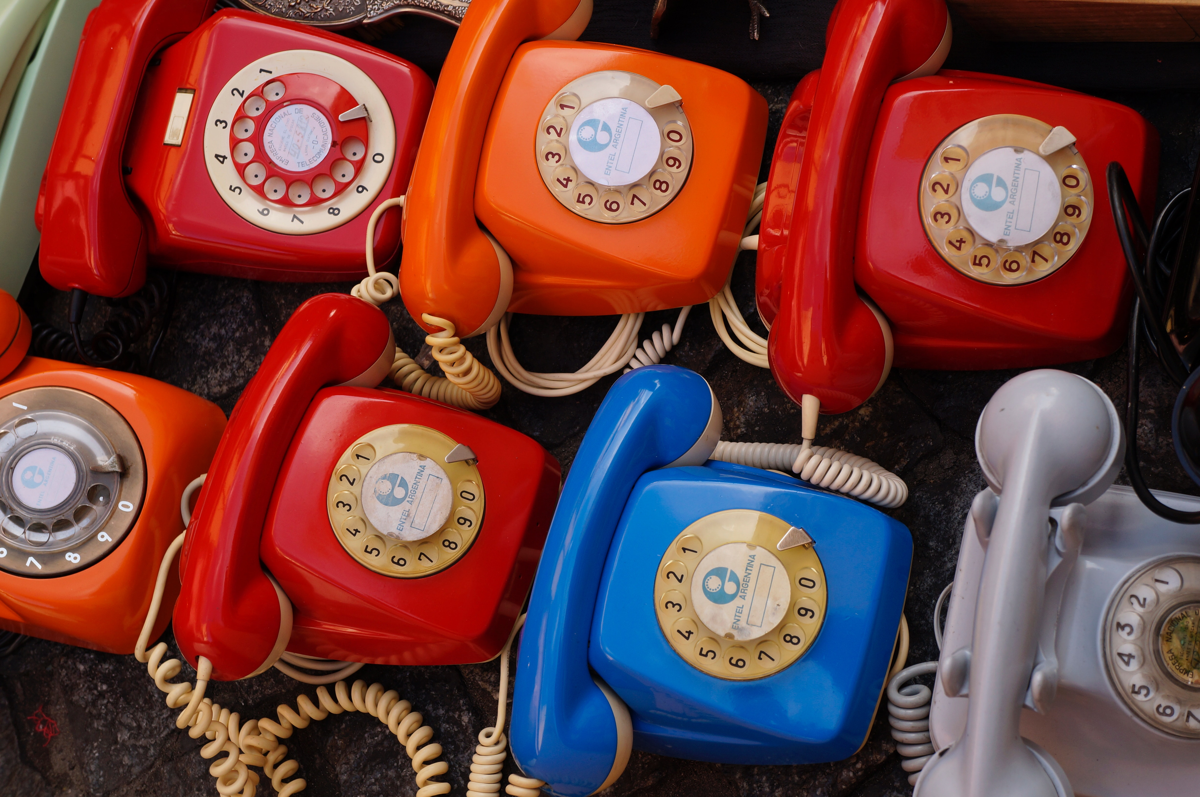 Seven assorted colored rotary telephones photo