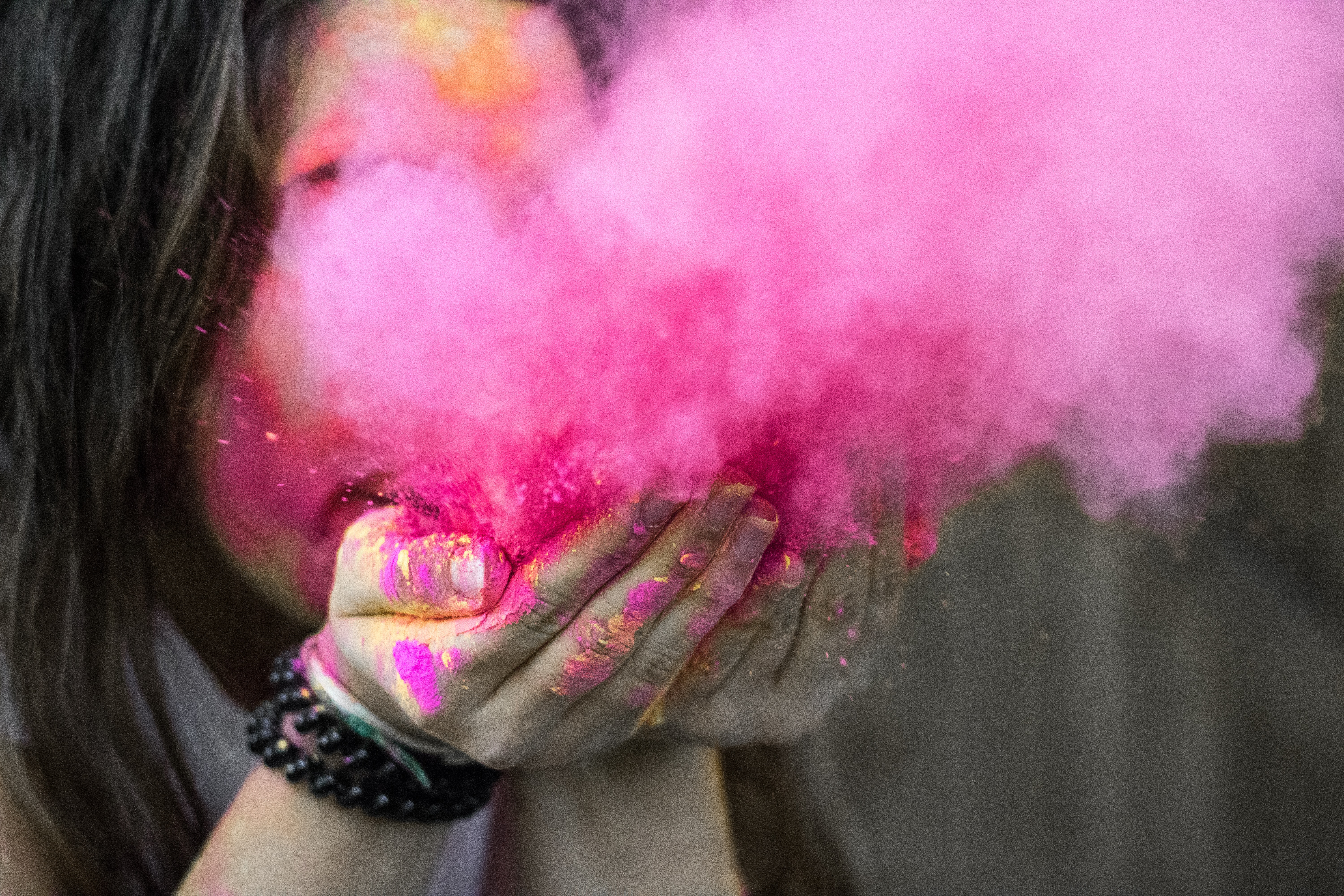 Shallow focus photograph of woman blowing pink powder