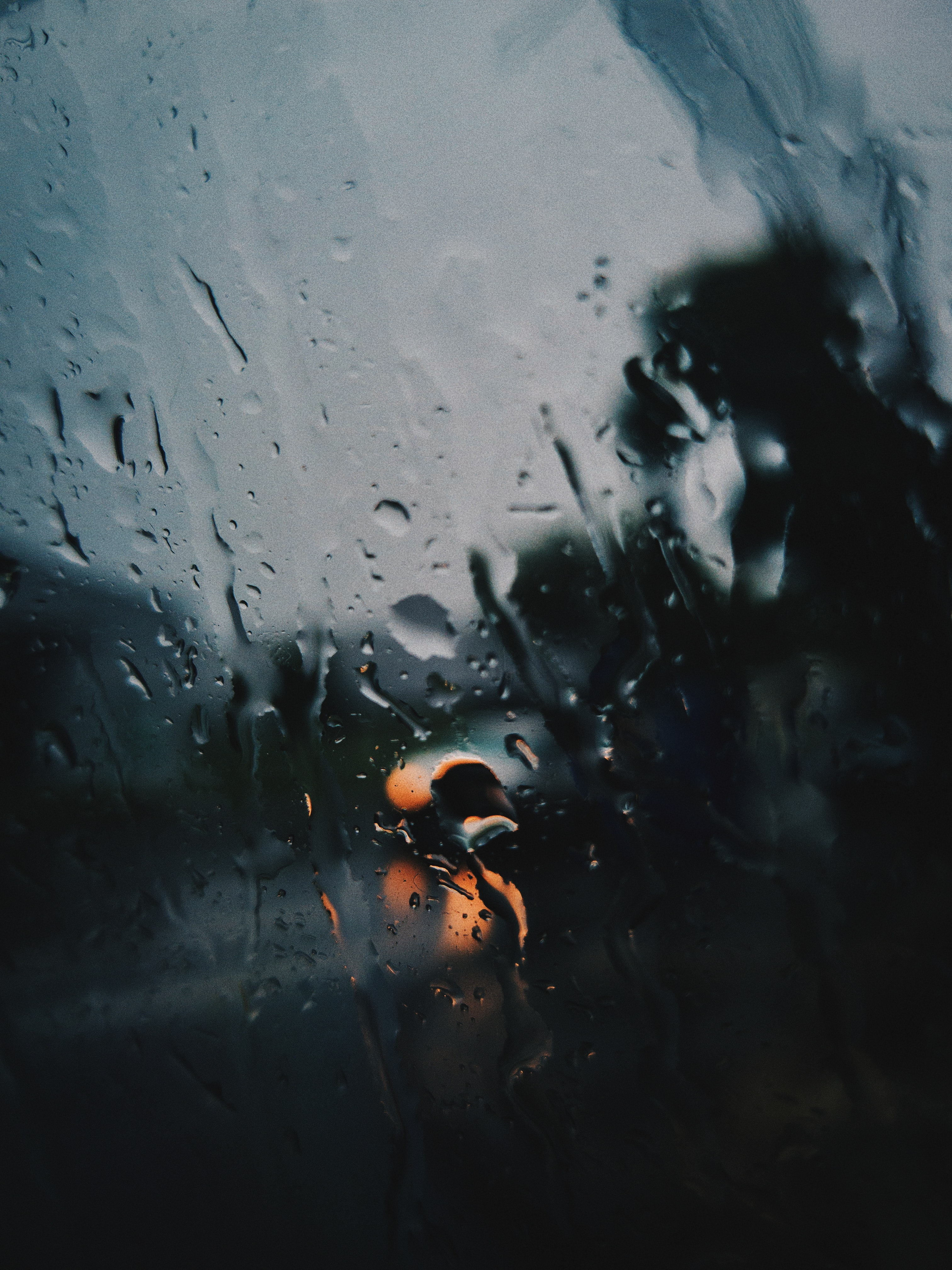 Shallow focus photography of rain on the window