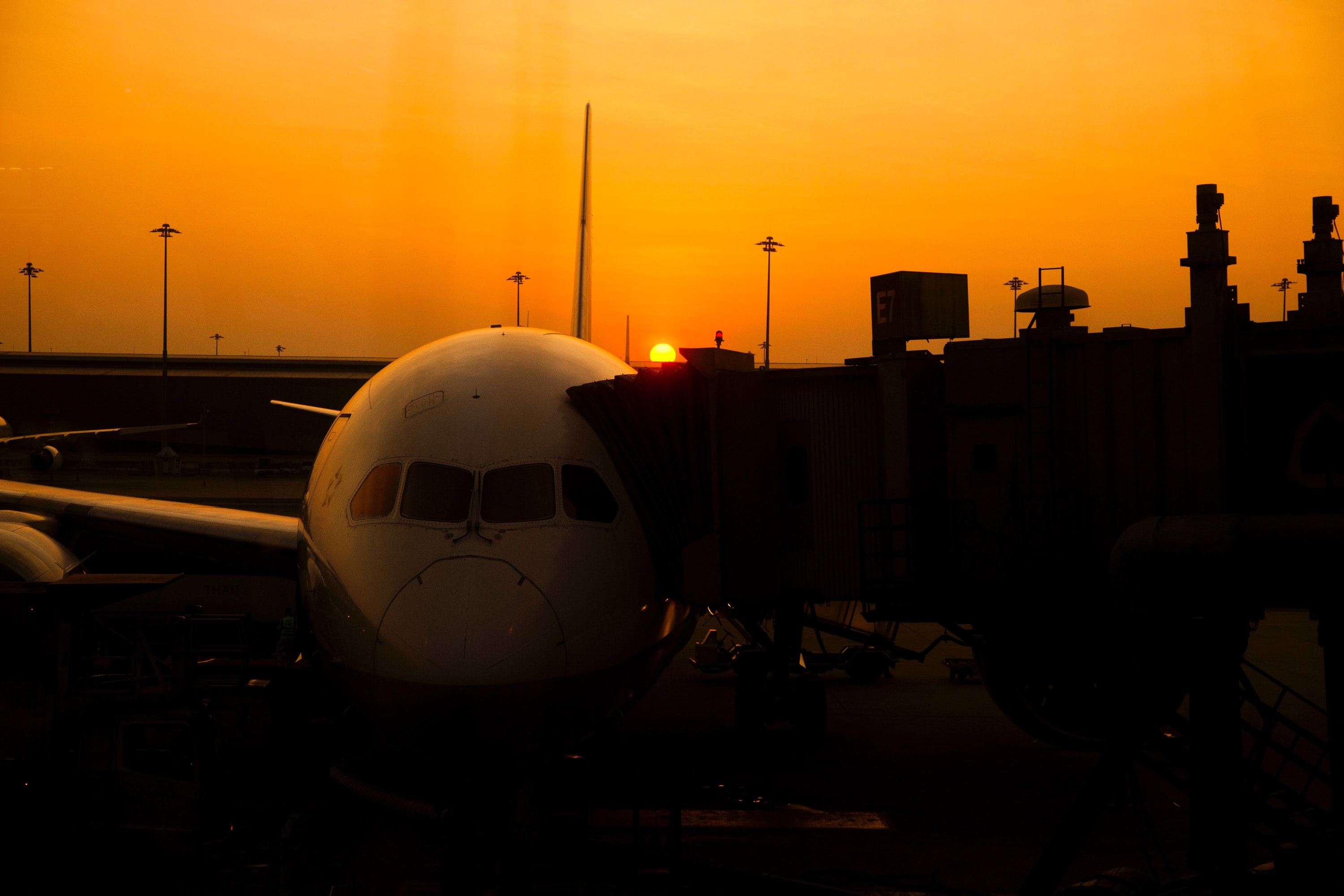 Silhouette of airplane on airport during sunset photo
