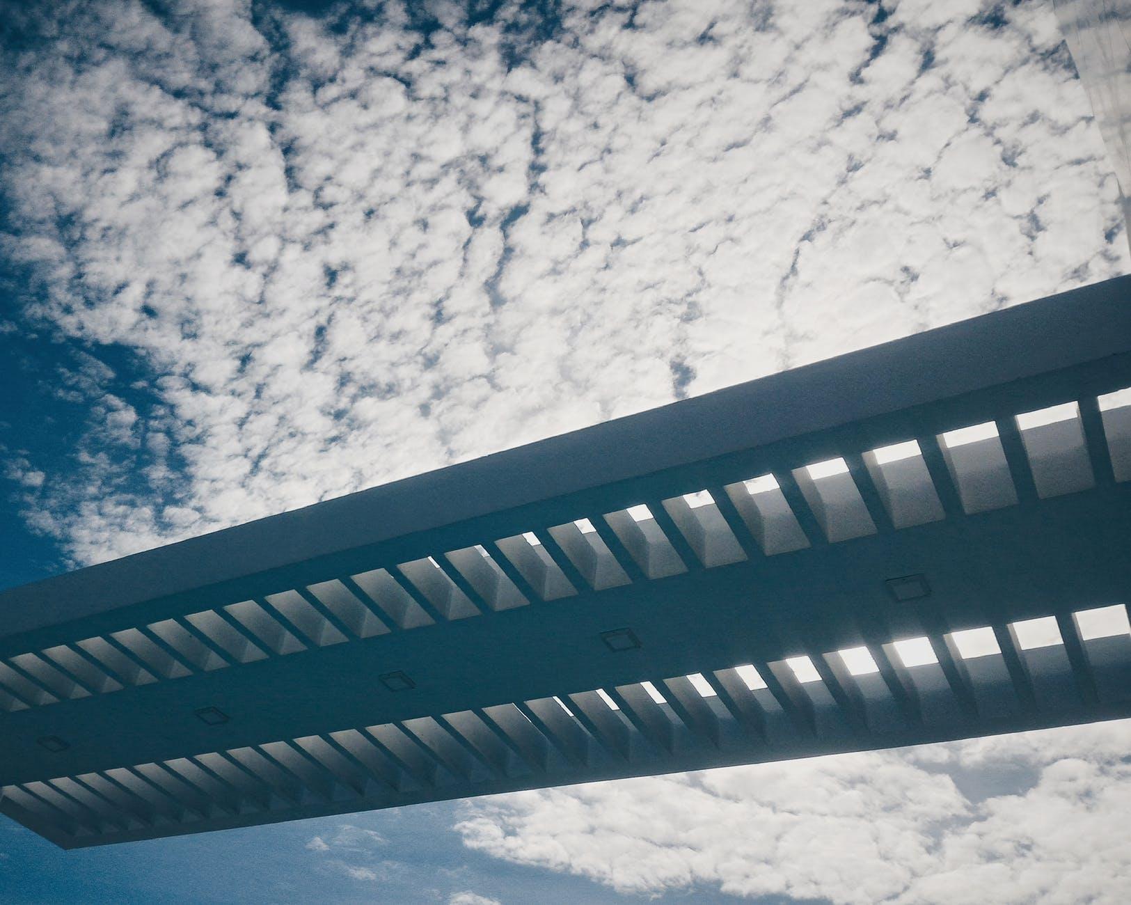 Silhouette of bridge under cloudy sky photo
