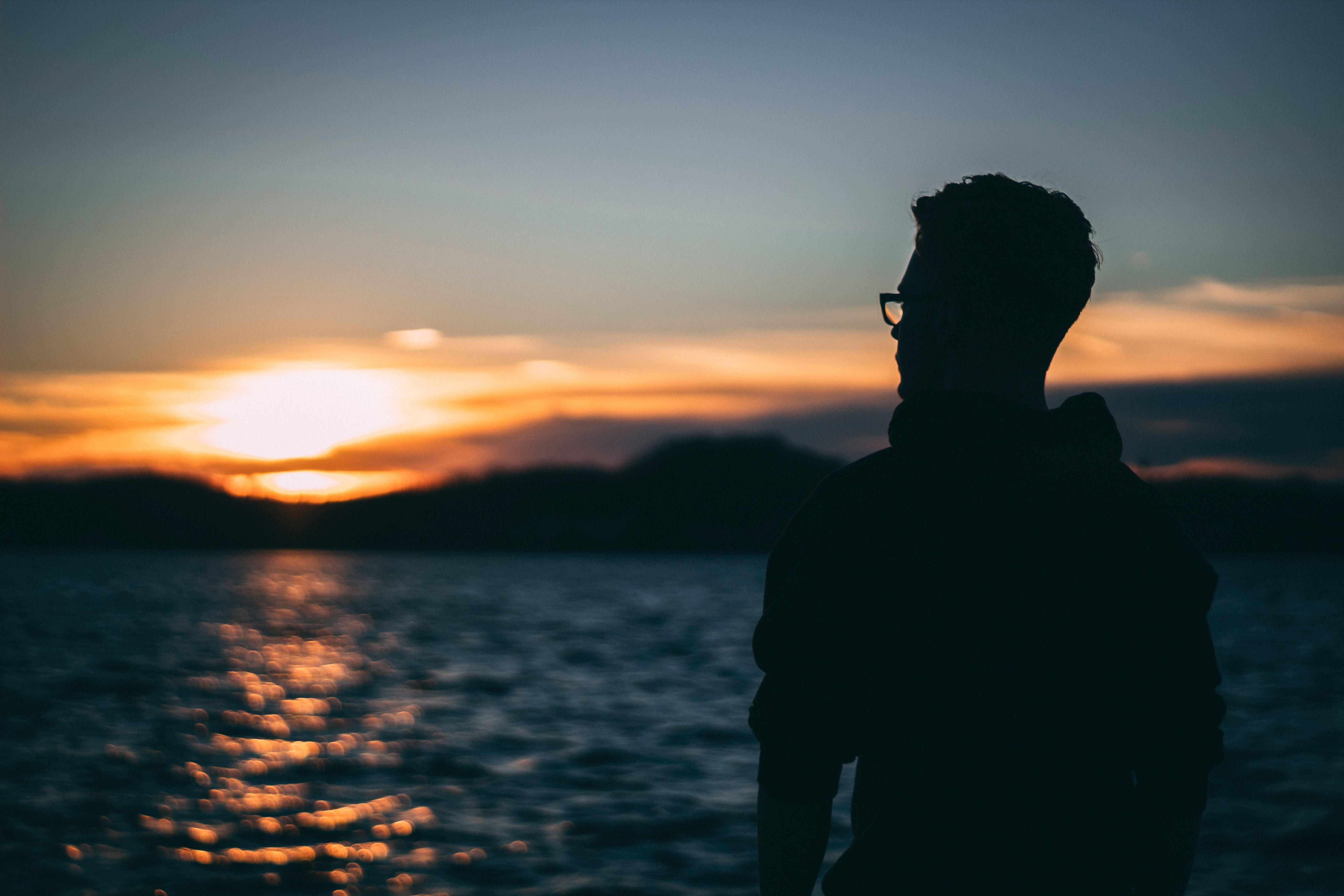 Free Photo Silhouette Of Man During Sunrise Backlit Sea Water