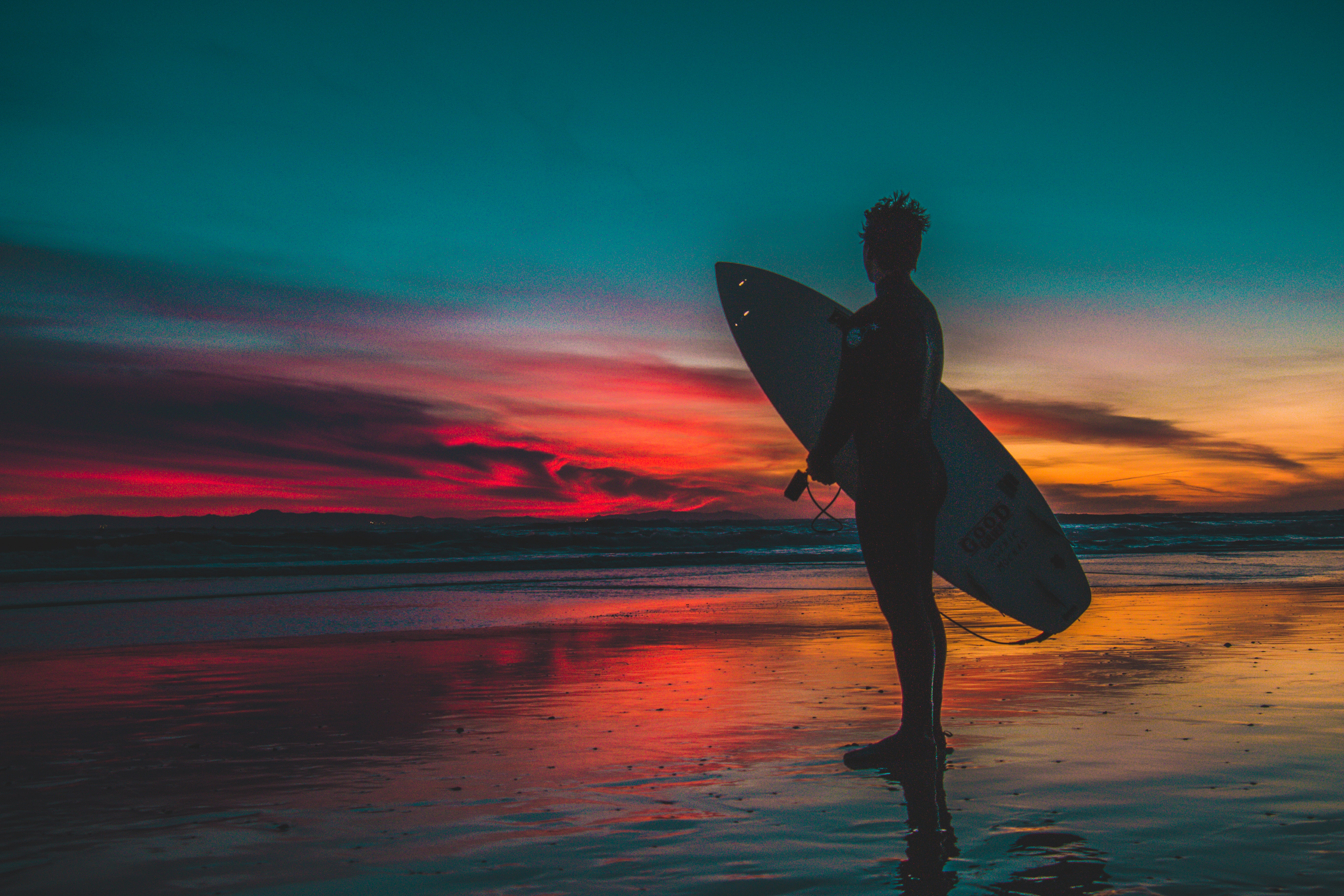 Silhouette of man in wet suit holding white surfboard while standing on beach during golden hour photo