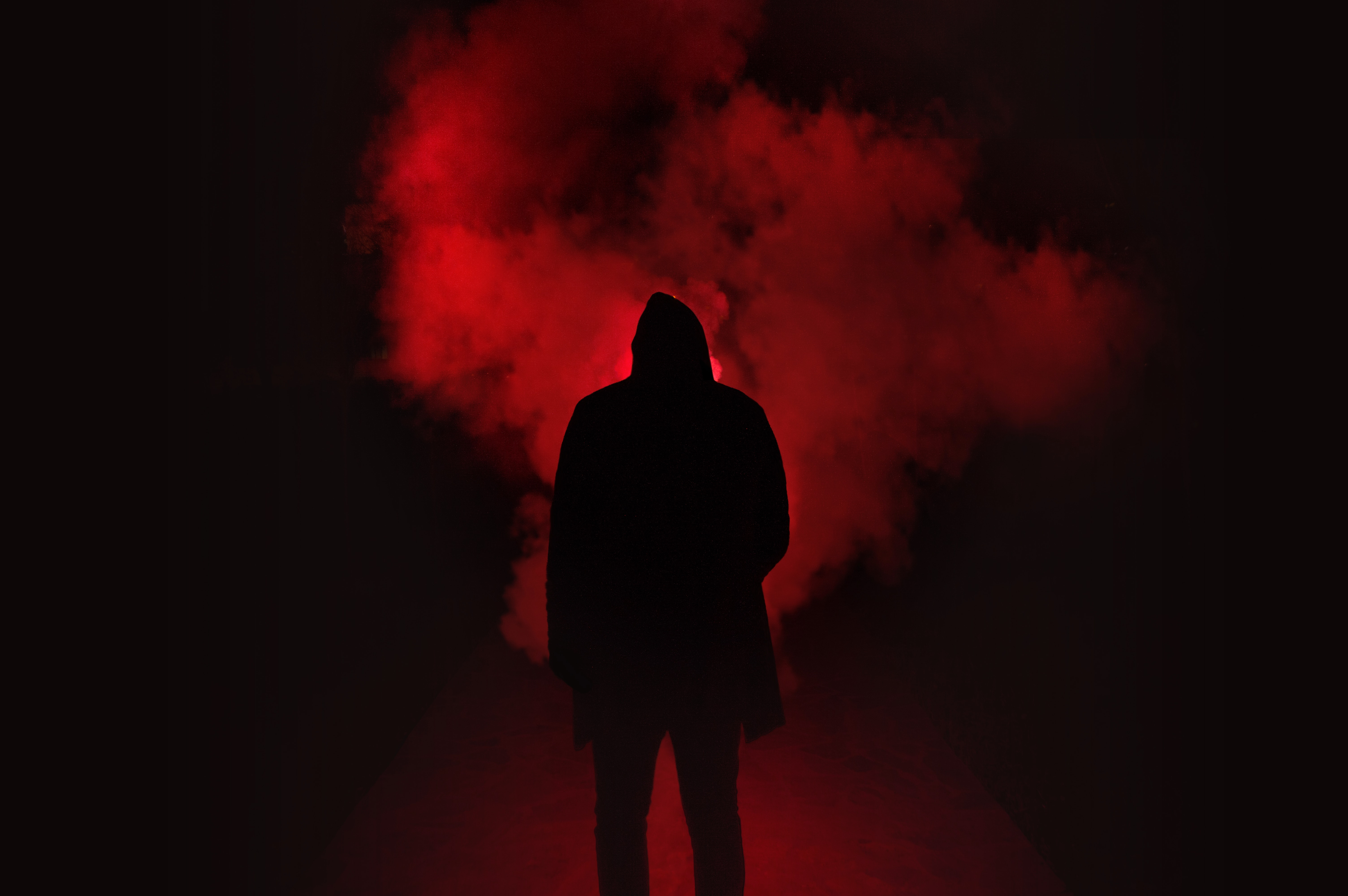 Silhouette of man standing against black and red background photo