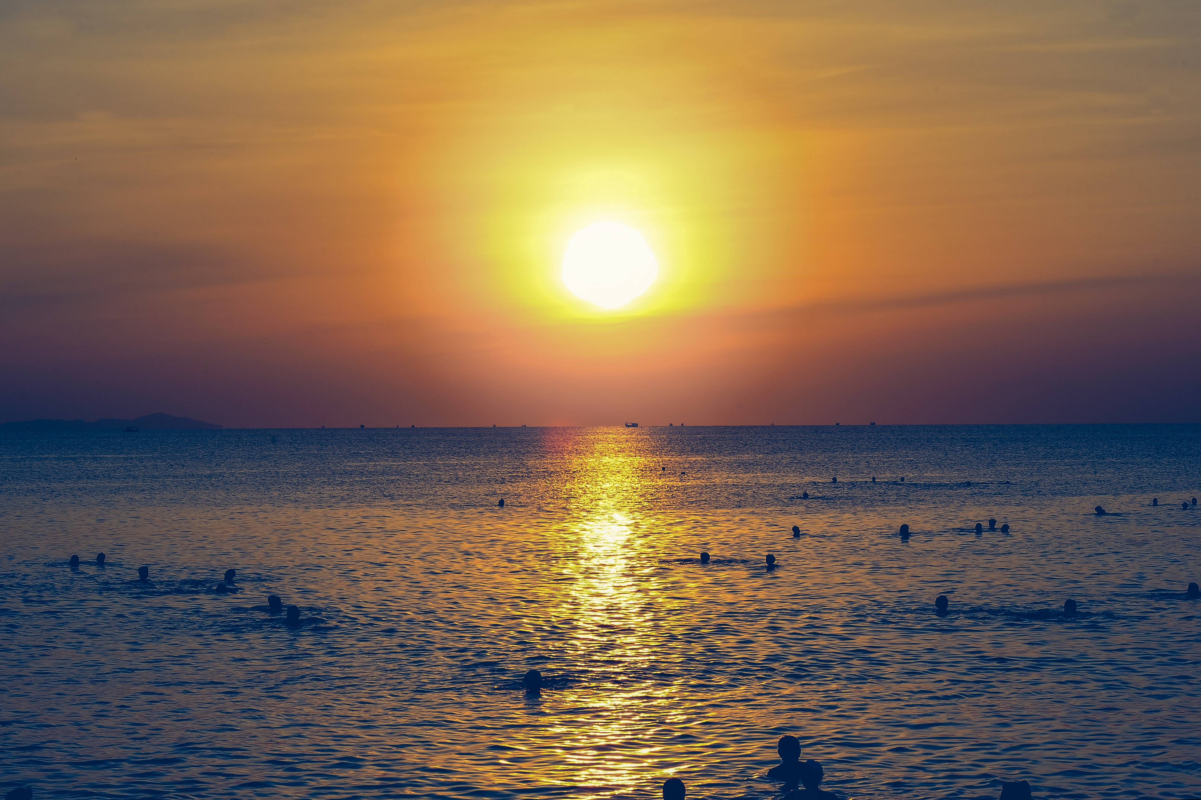 Silhouette of people swimming in the ocean during sunset photo