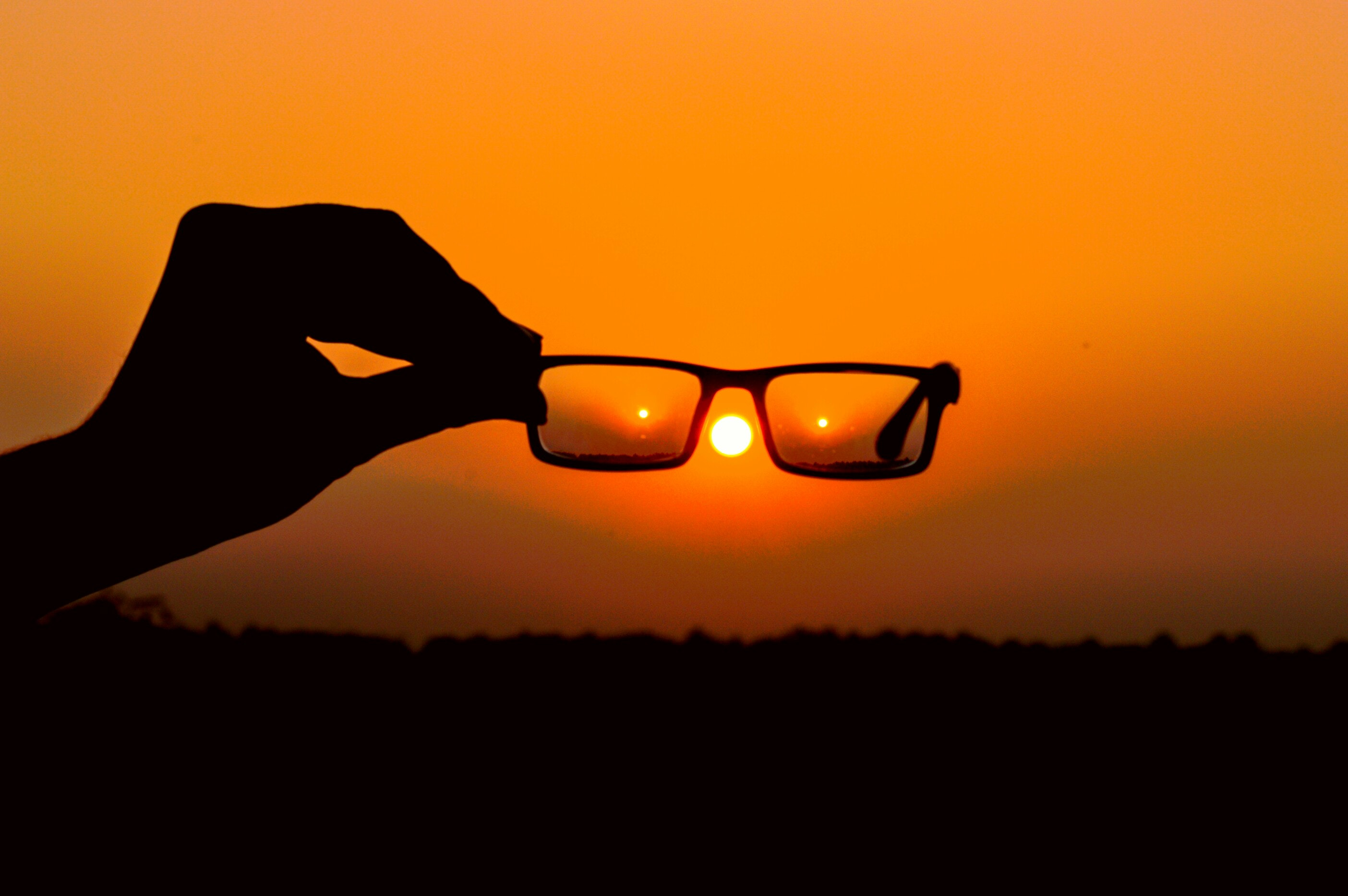 Silhouette of person's hand holding eyeglasses during golden hour photo