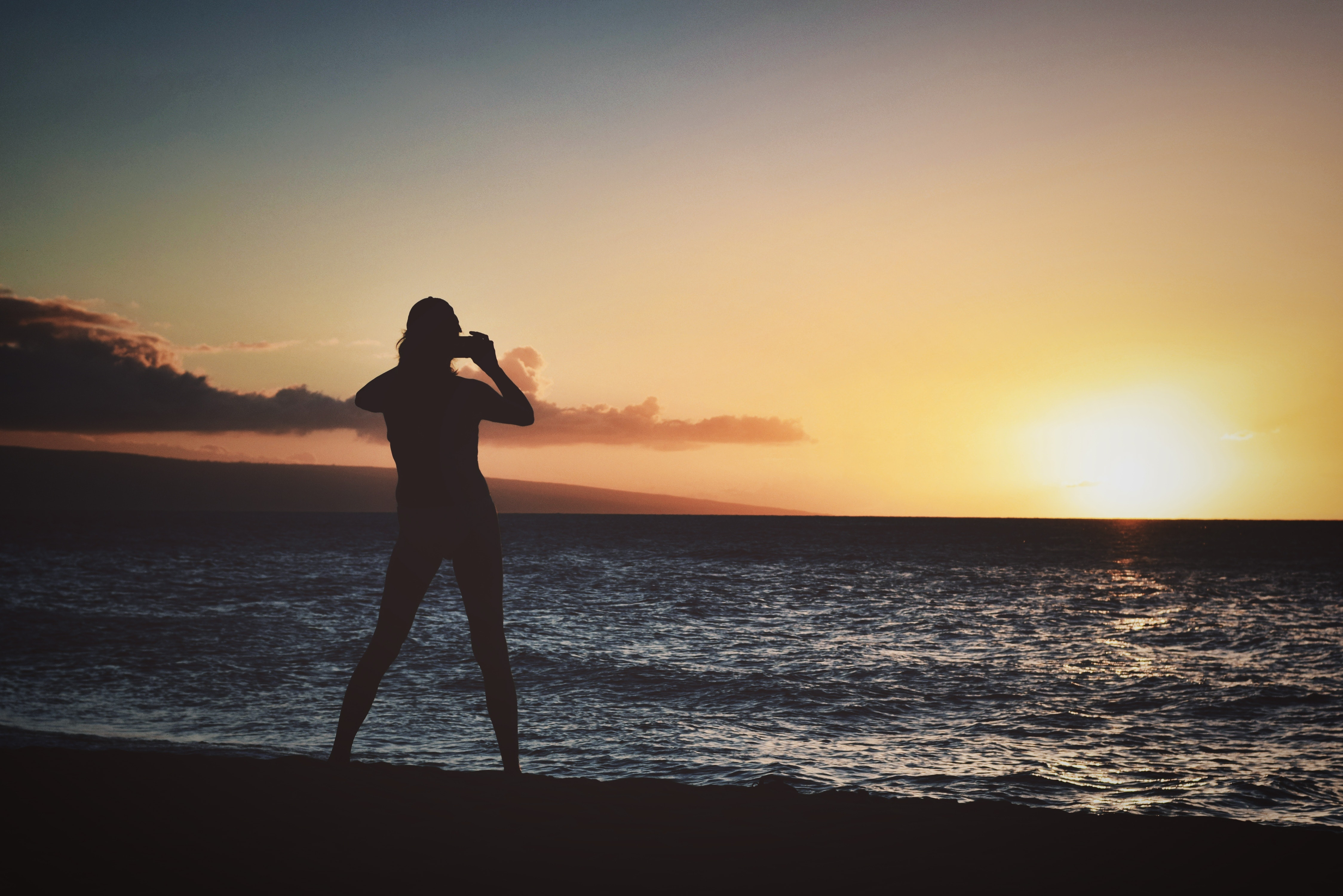 Silhouette of woman holding camera near seashore during golden hour photo