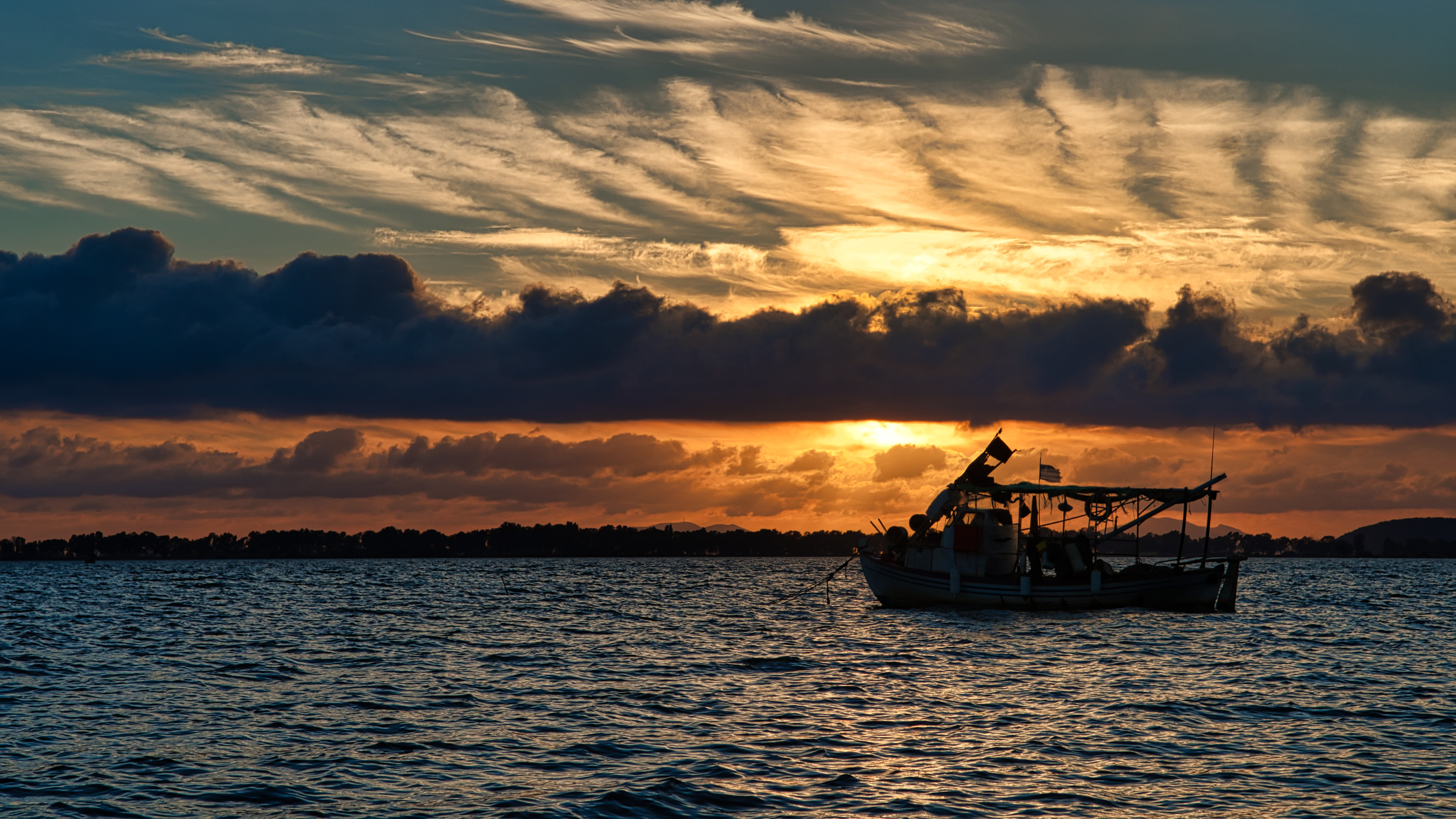 Silhouette photo of boat on ocean during golden hour