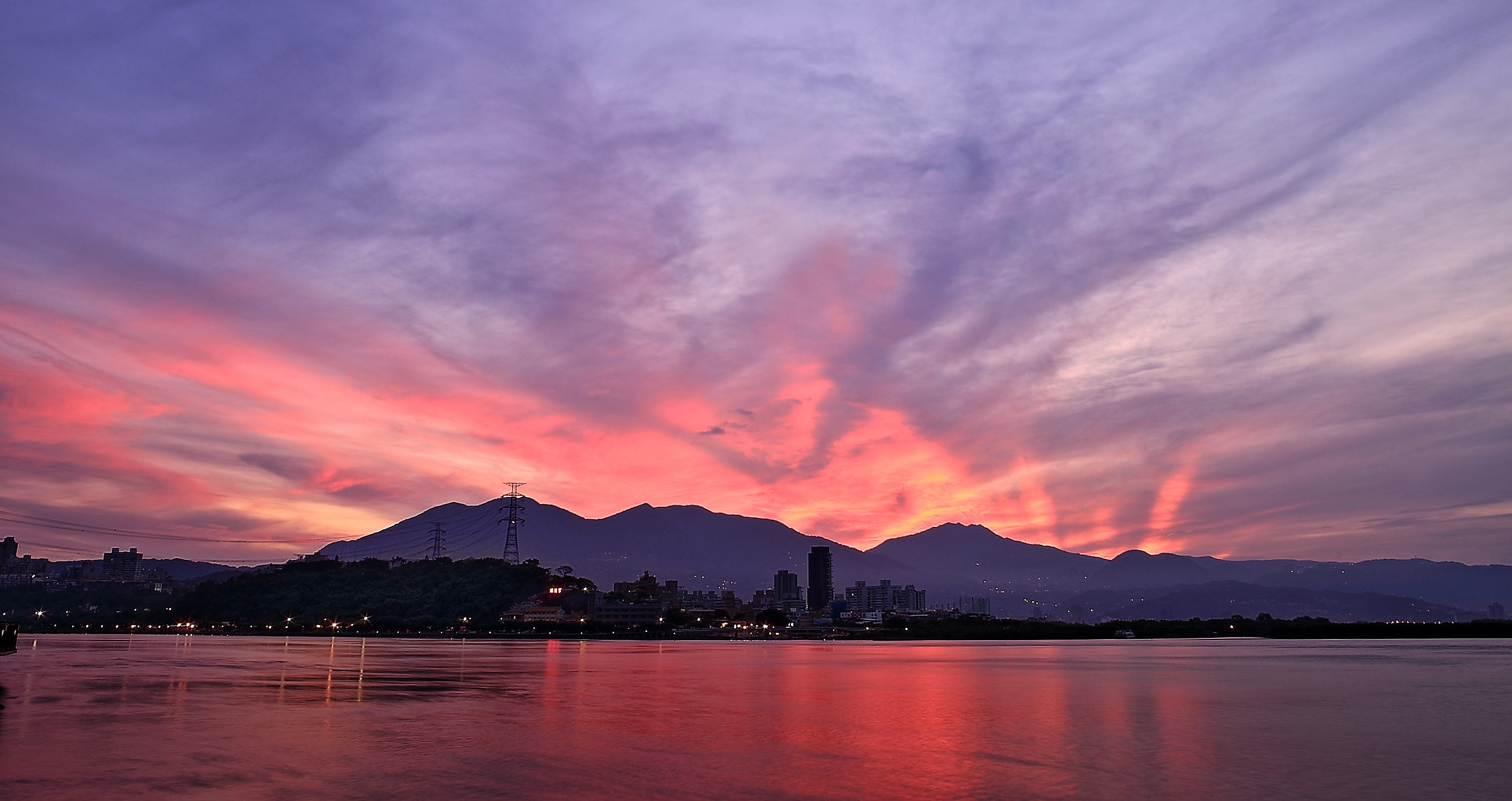 Silhouette photo of city buildings near sea with mountain during golden time