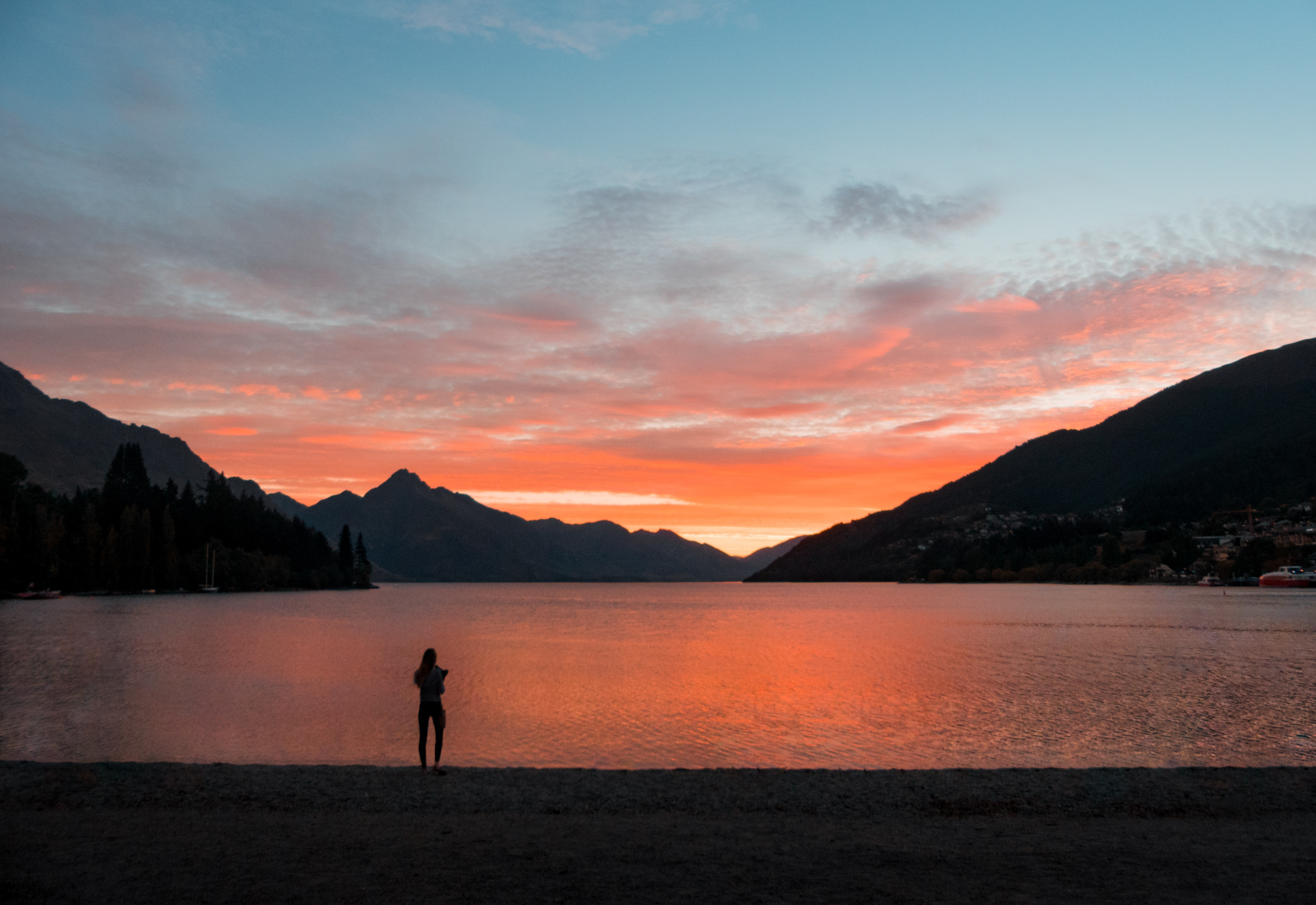 Silhouette photo of person standing near body of water
