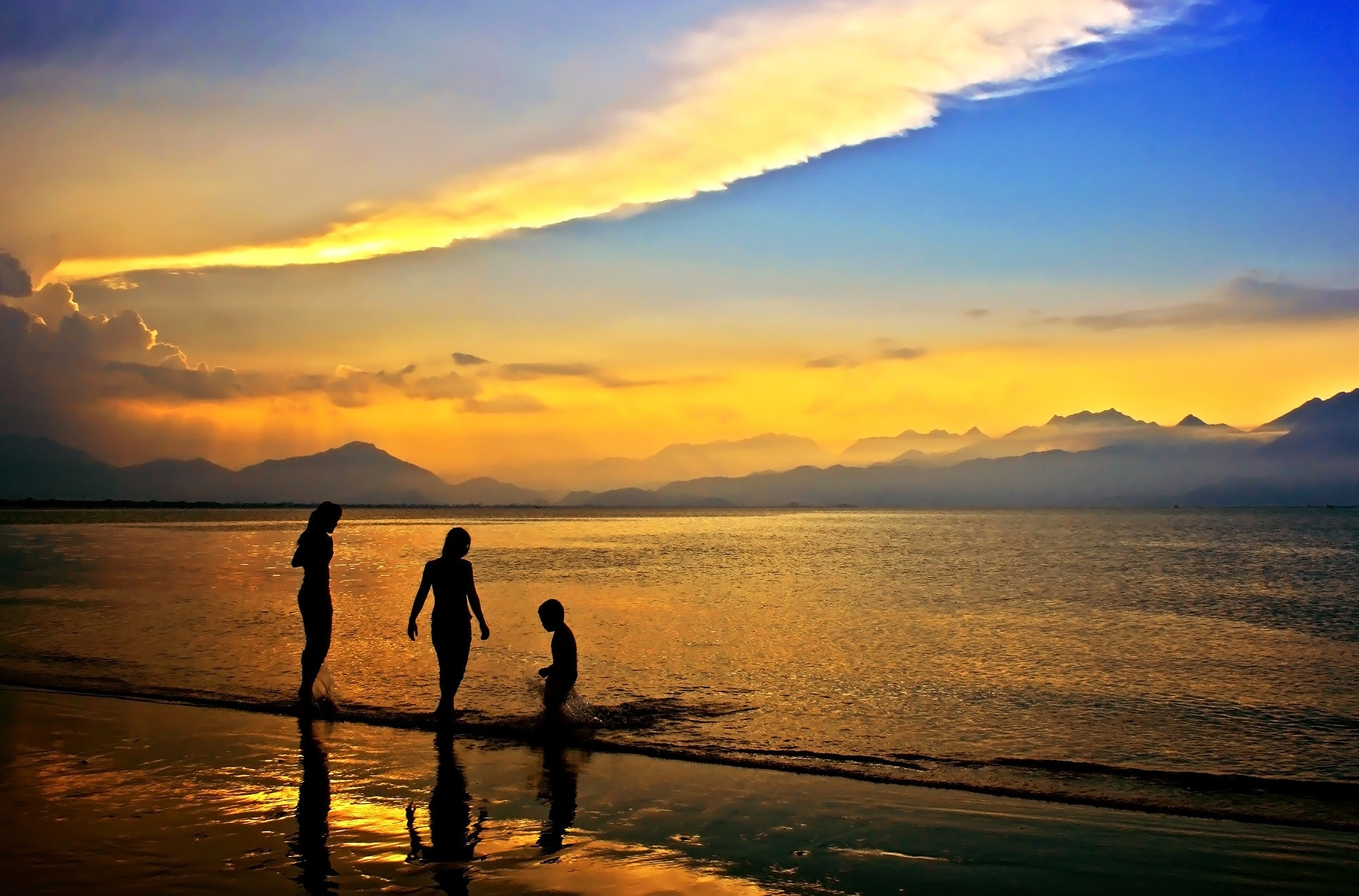 Silhouettes of 3 people in body of water during dawn photo