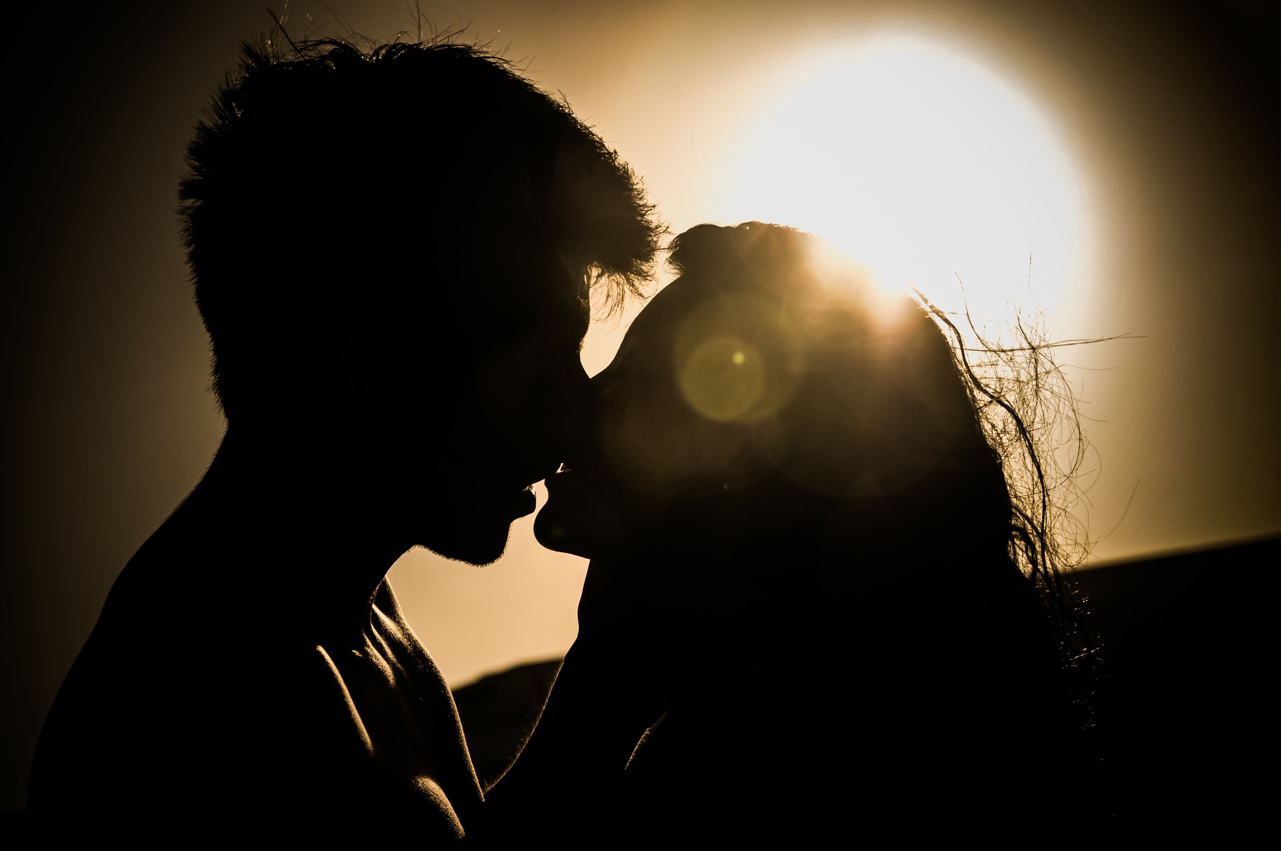 Silhouettes of couple kissing against sunset photo