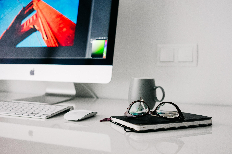 Silver Imac Turned on Beside Gray Ceramic Mug and Black Frame Eyeglasses, Notebook, Monitor, Office, Screen, HQ Photo
