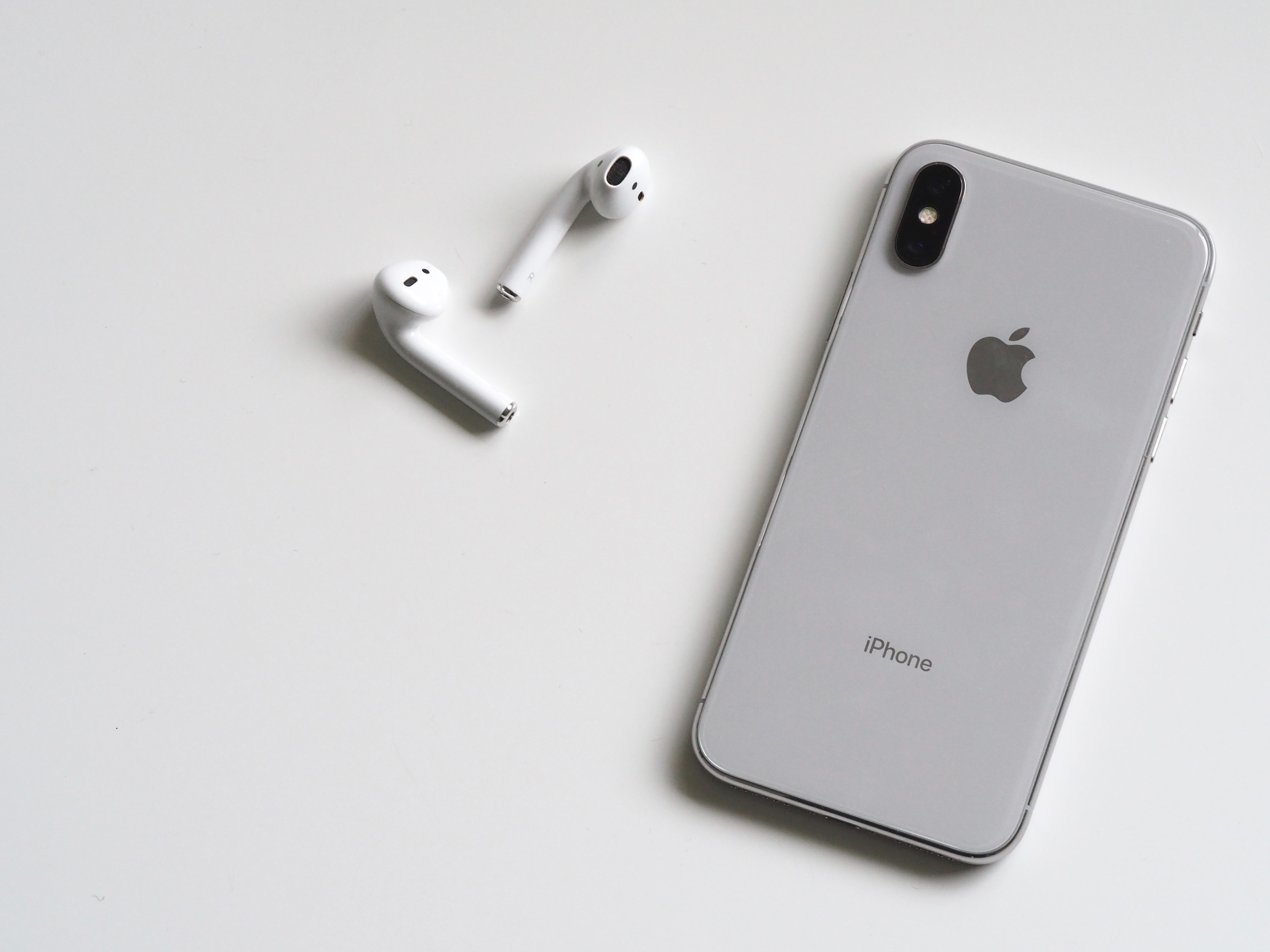 Silver iphone x with airpods photo
