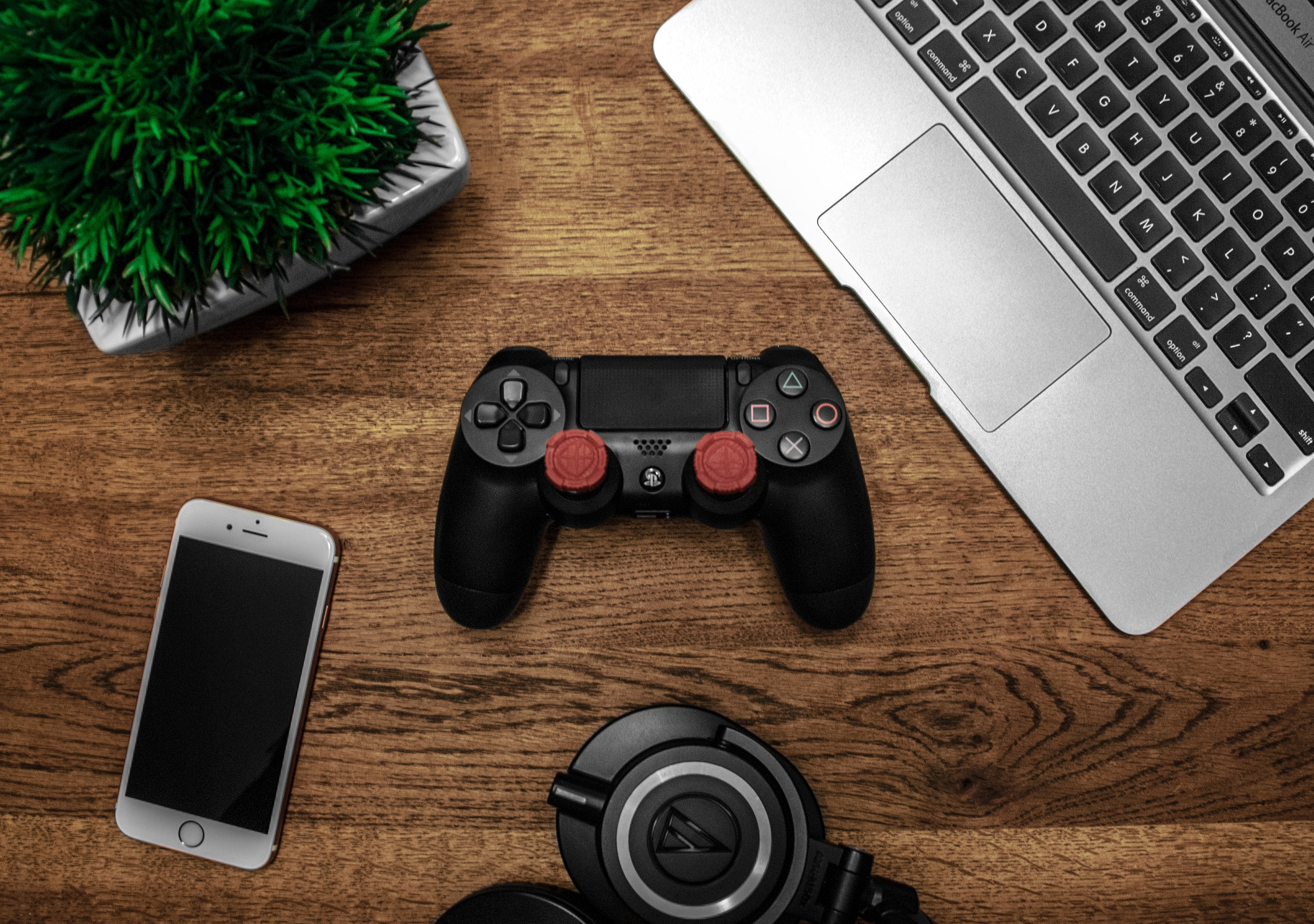 Silver macbook beside black sony ps4 dualshock 4, silver iphone 6, and round black keychain on brown wooden table photo