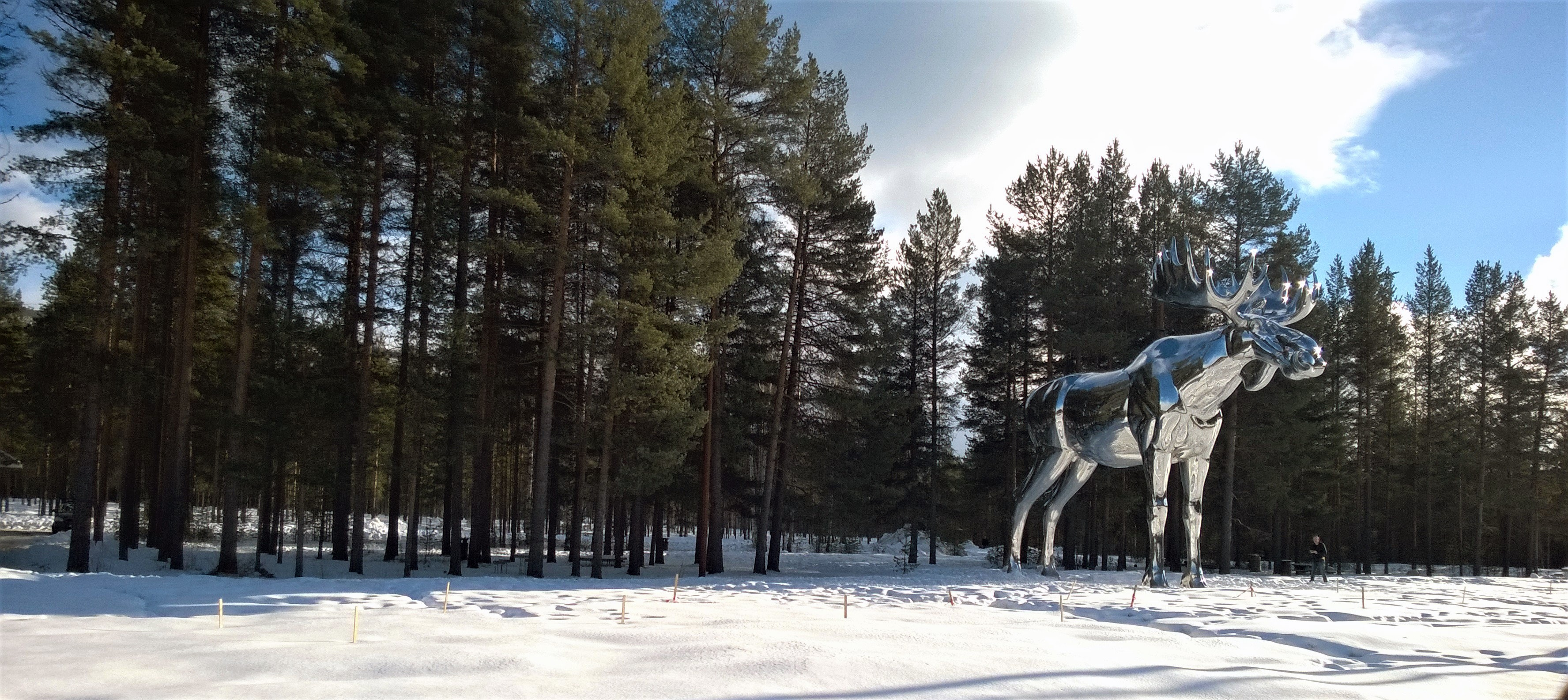 Silver moose statue near tree photo