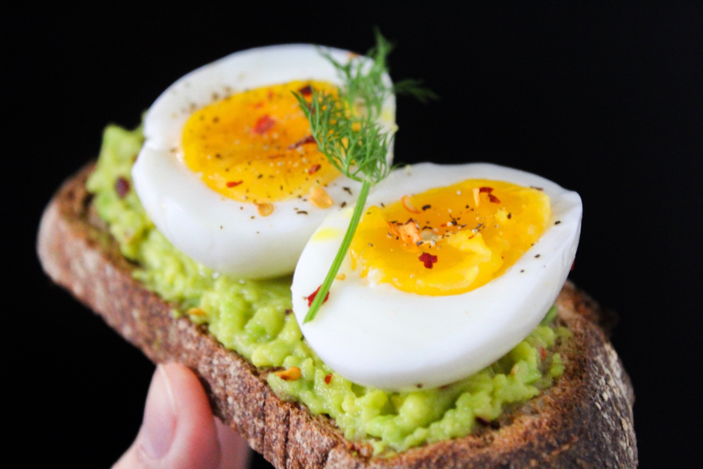 Sliced egg on top of green salad with bread photo