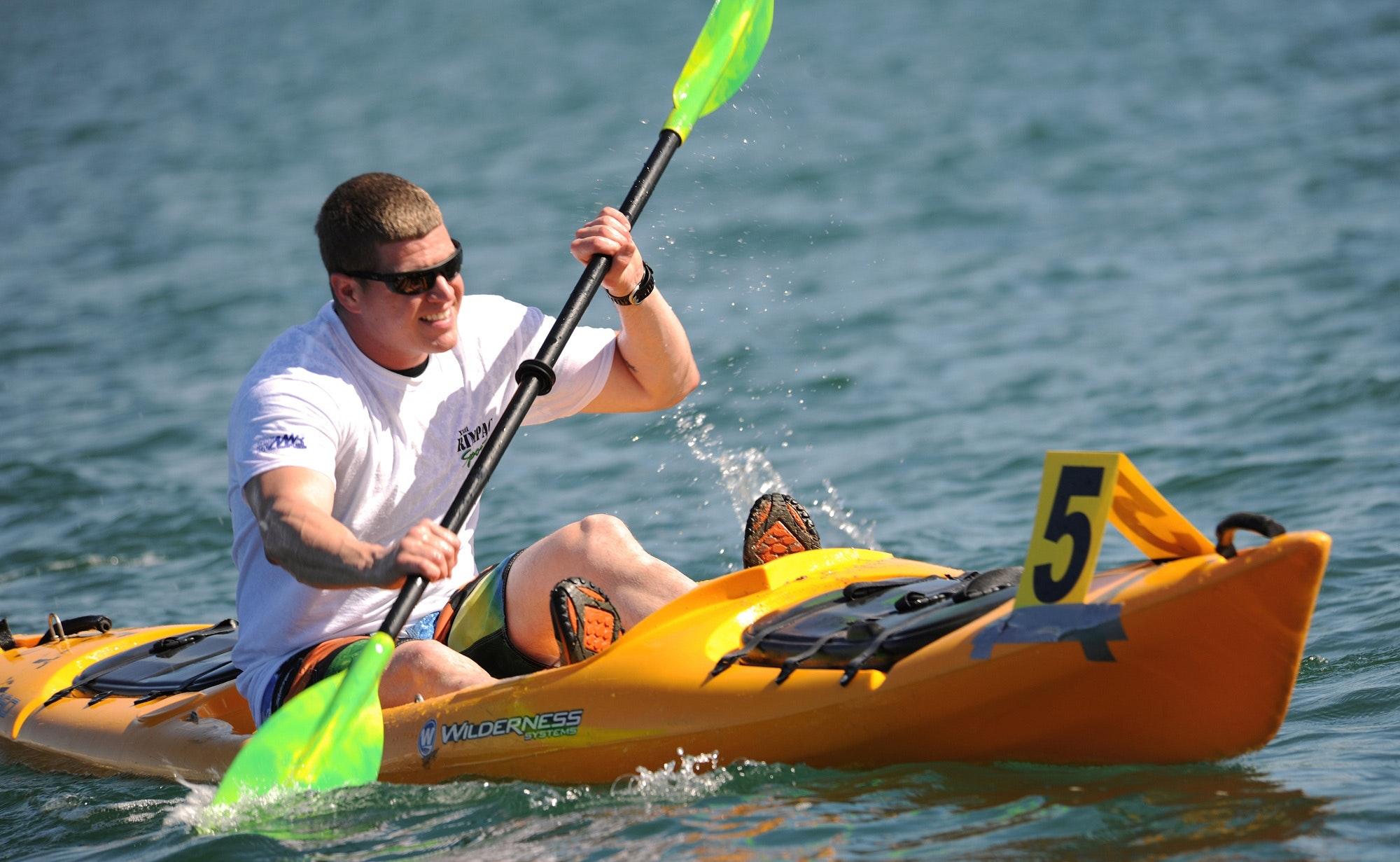 Smiling man in white crew neck t shirt wearing sunglasses paddling on yellow kayak during daytime photo