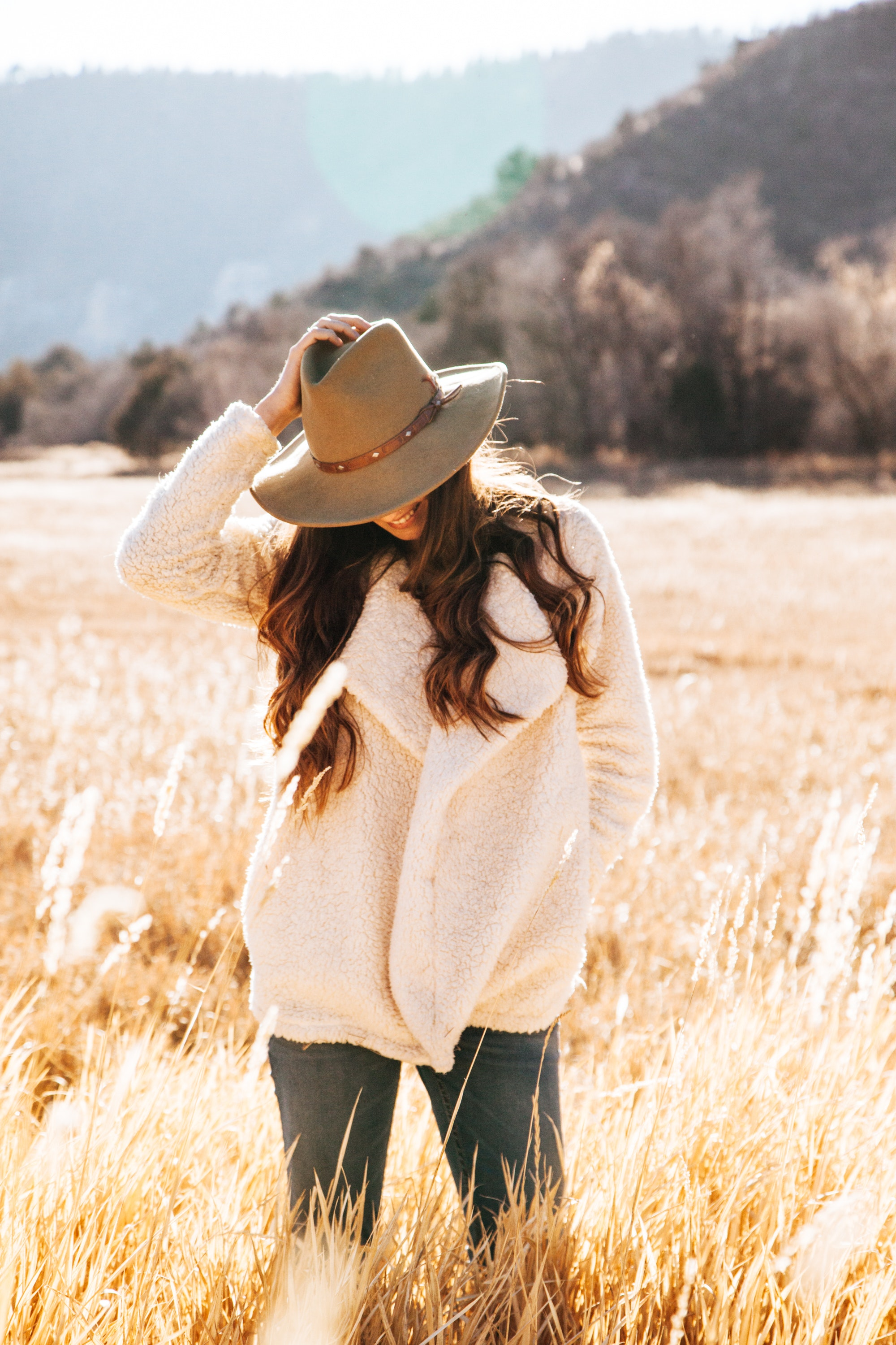 Smiling woman in white winter jacket wearing brown cowboy hat surrounded of brown grass field photo